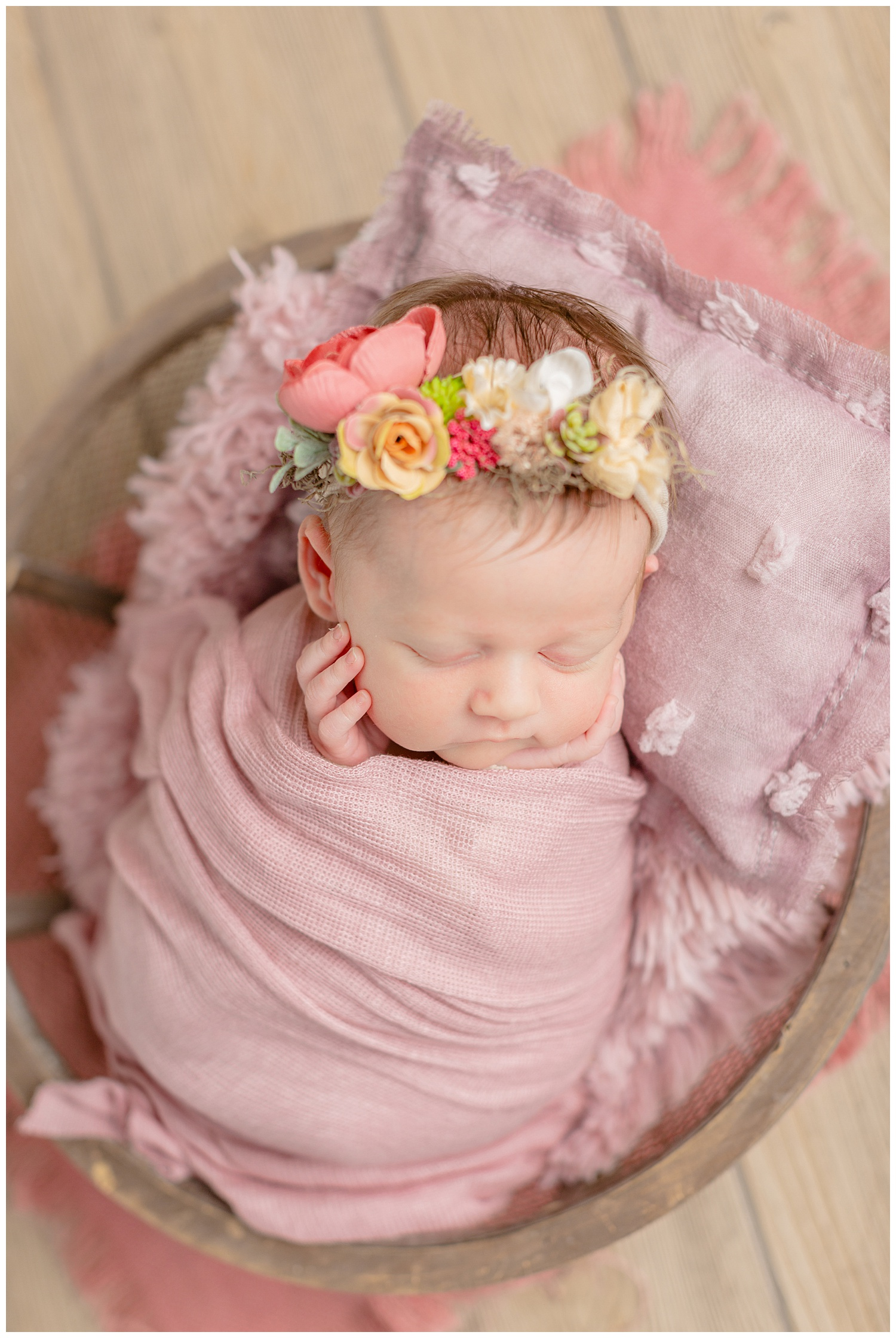 Newborn baby girl wrapped in a mauve colored stretch fabric snuggled in a basket bowl wearing a garden floral headband.   CB Studio