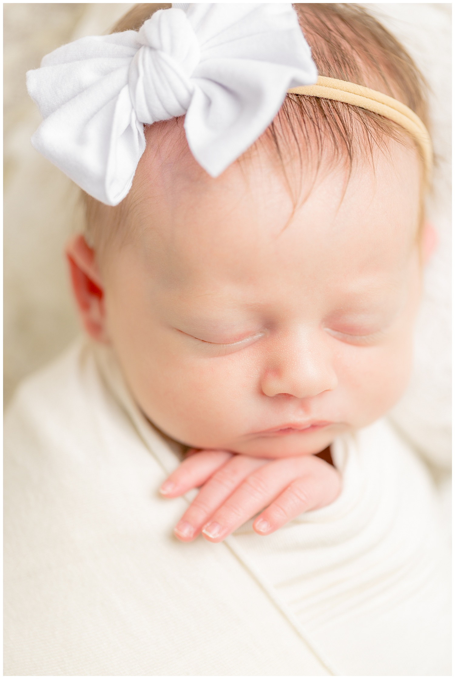 Newborn baby girl wrapped in ivory stretch fabric resting her chin gently on her hand while wearing a white bow headband.   CB Studio