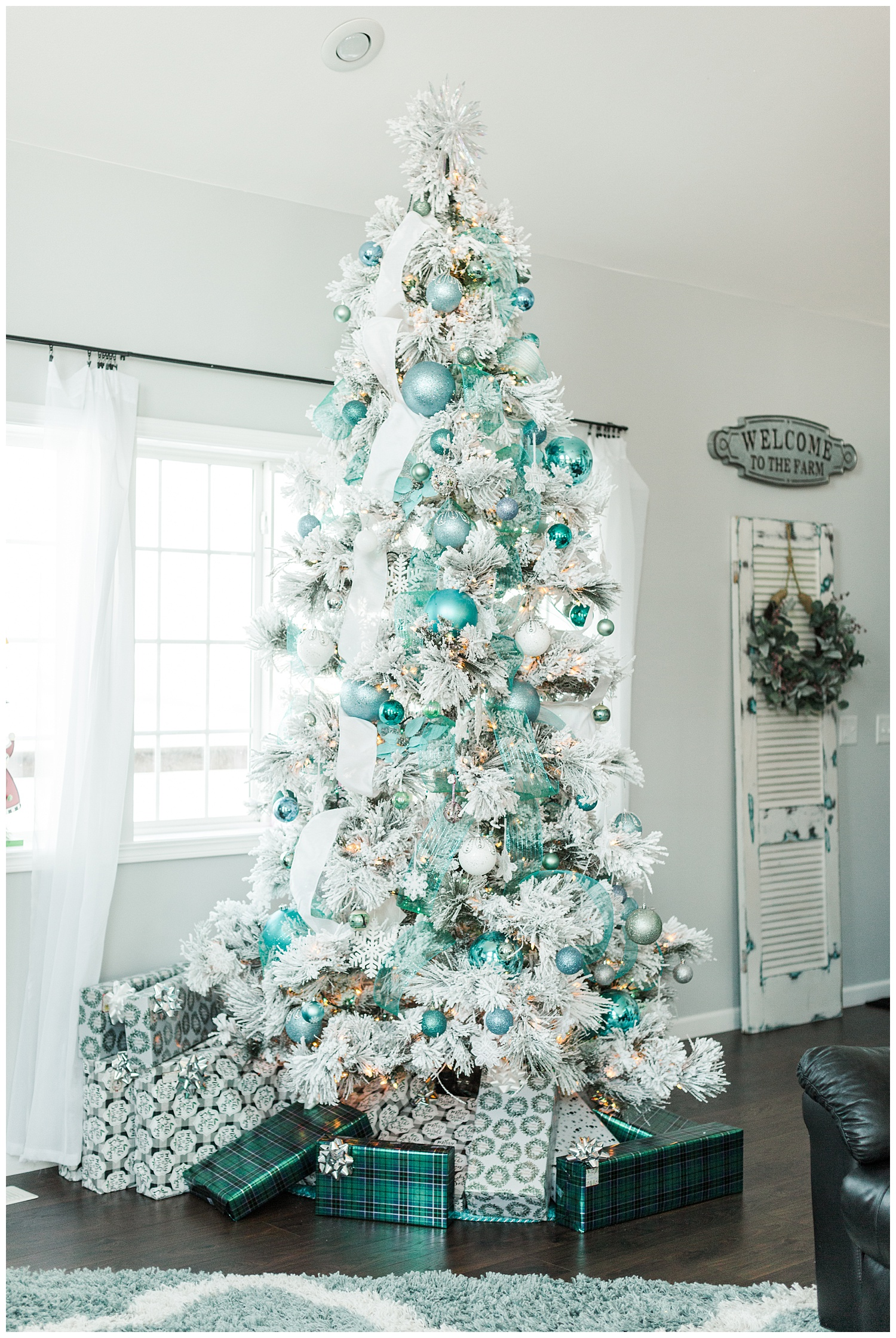 Flocked Christmas tree decorated with white and teal ribbon and teal, light blue and aqua ornaments | CB Studio