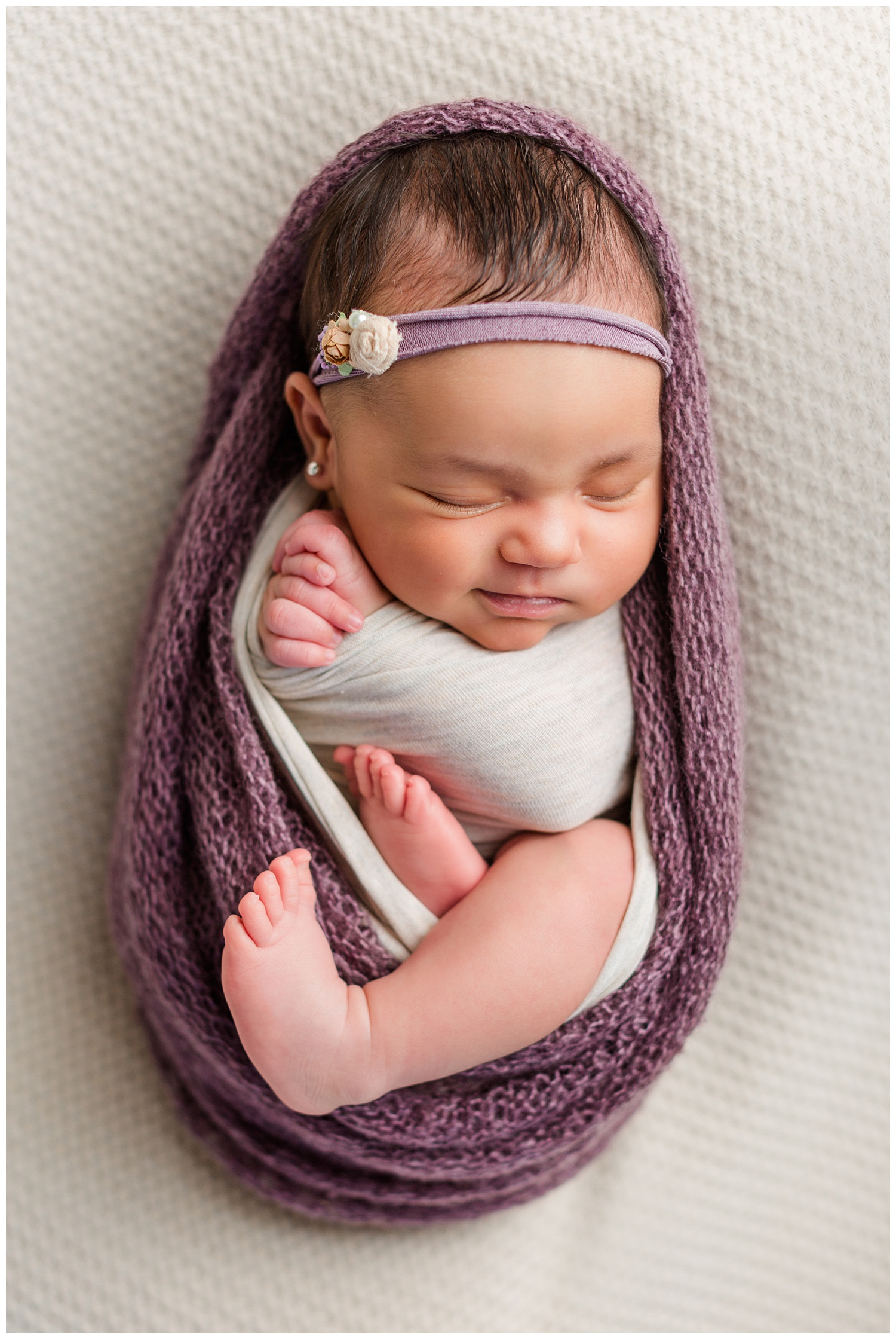 Newborn baby Alyssa wrapped up in a puprle knit wrap with her hands folded in prayer and smiling | CB Studio