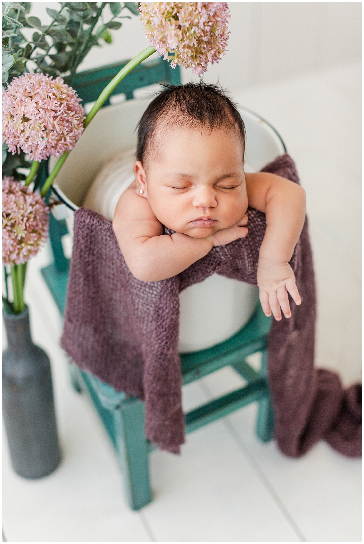 Newborn baby Alyssa snuggled in a white bucket resting on a teal chair with beautiful pink florals surrounding her | CB Studio