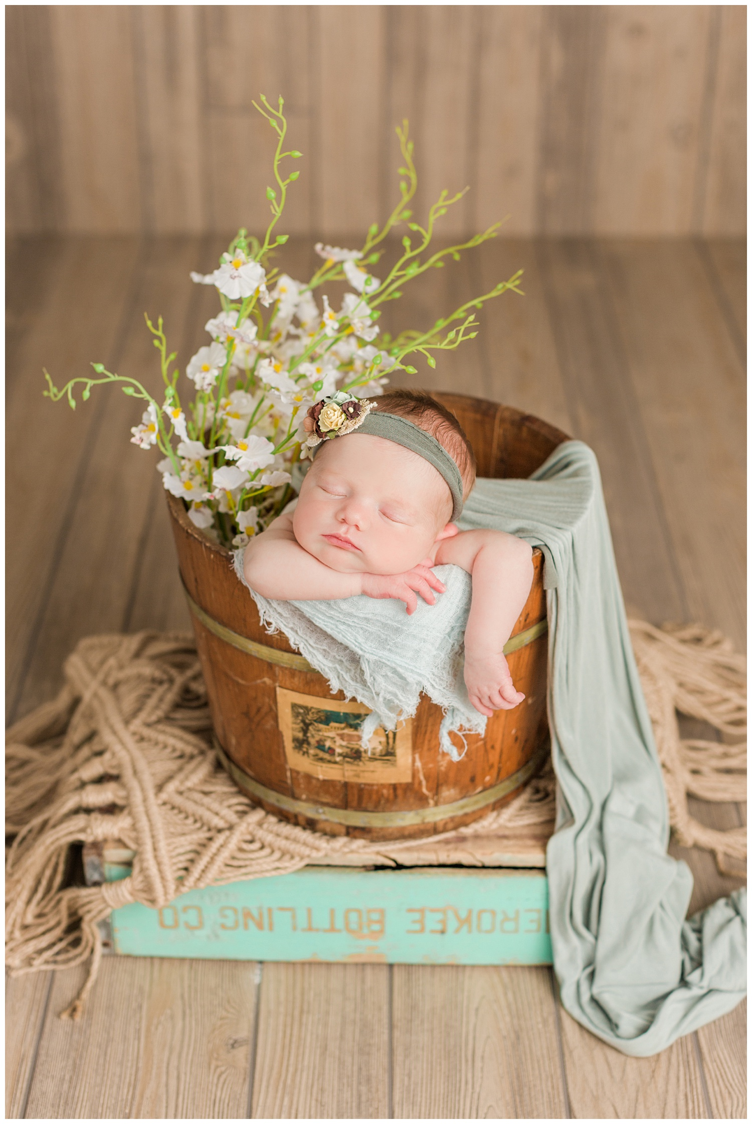 Baby Scarlett posed in a rustic bucket and box with white florals and pops of sage and mint | CB Studio