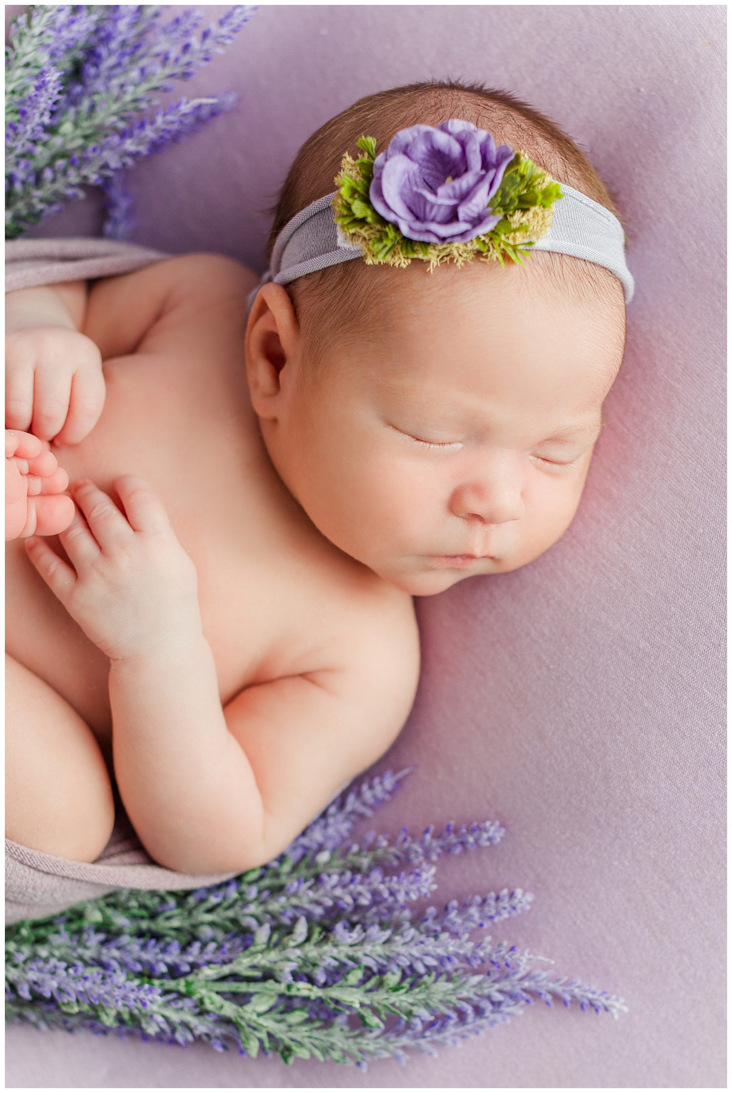 Baby Emma snuggled up with purple tones and spring florals | CB Studio