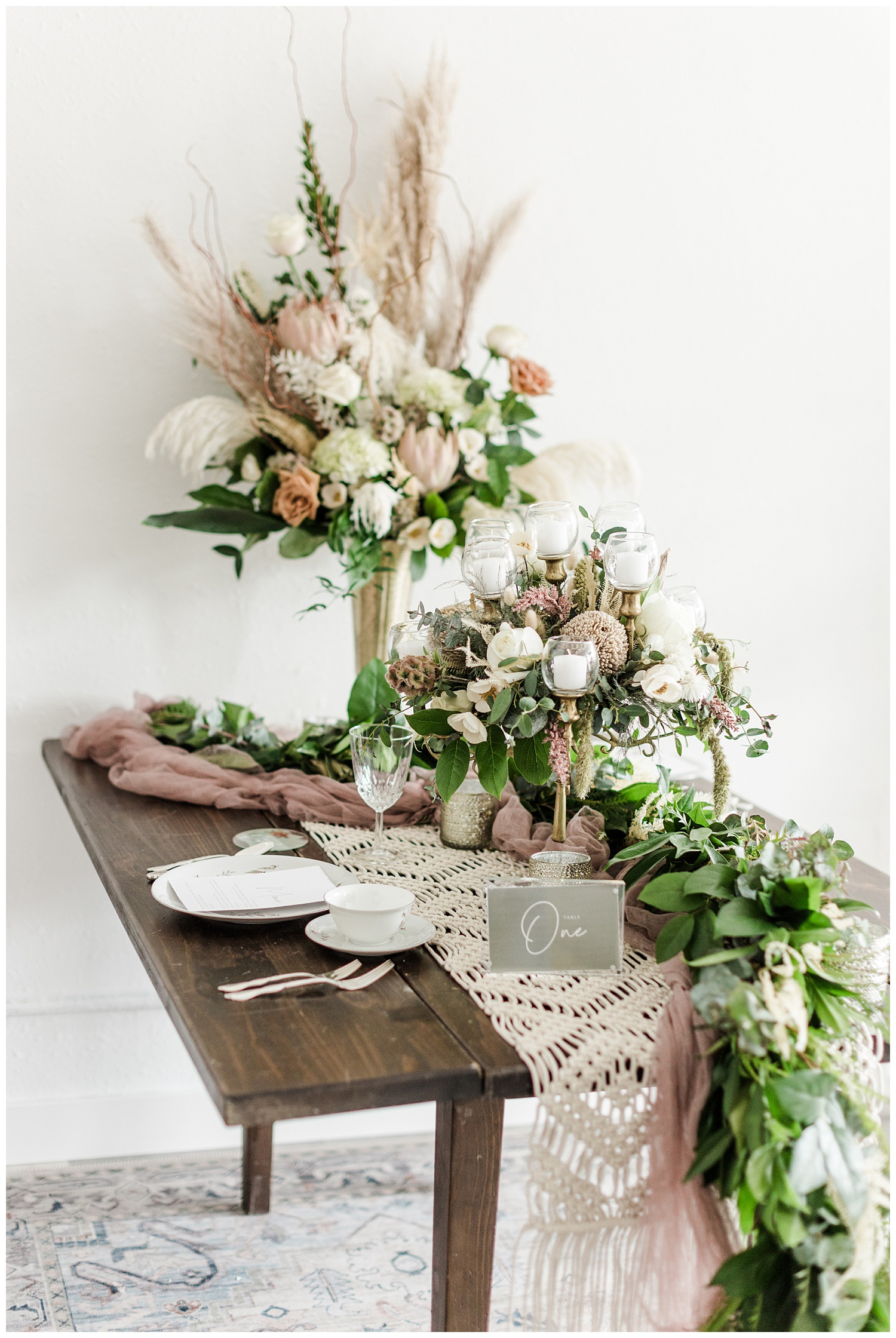 Vintage blush wedding tablescape complete with a gold candelabra, dried florals with pampas grass, macrame and eucalyptus table runner and antique china | CB Studio