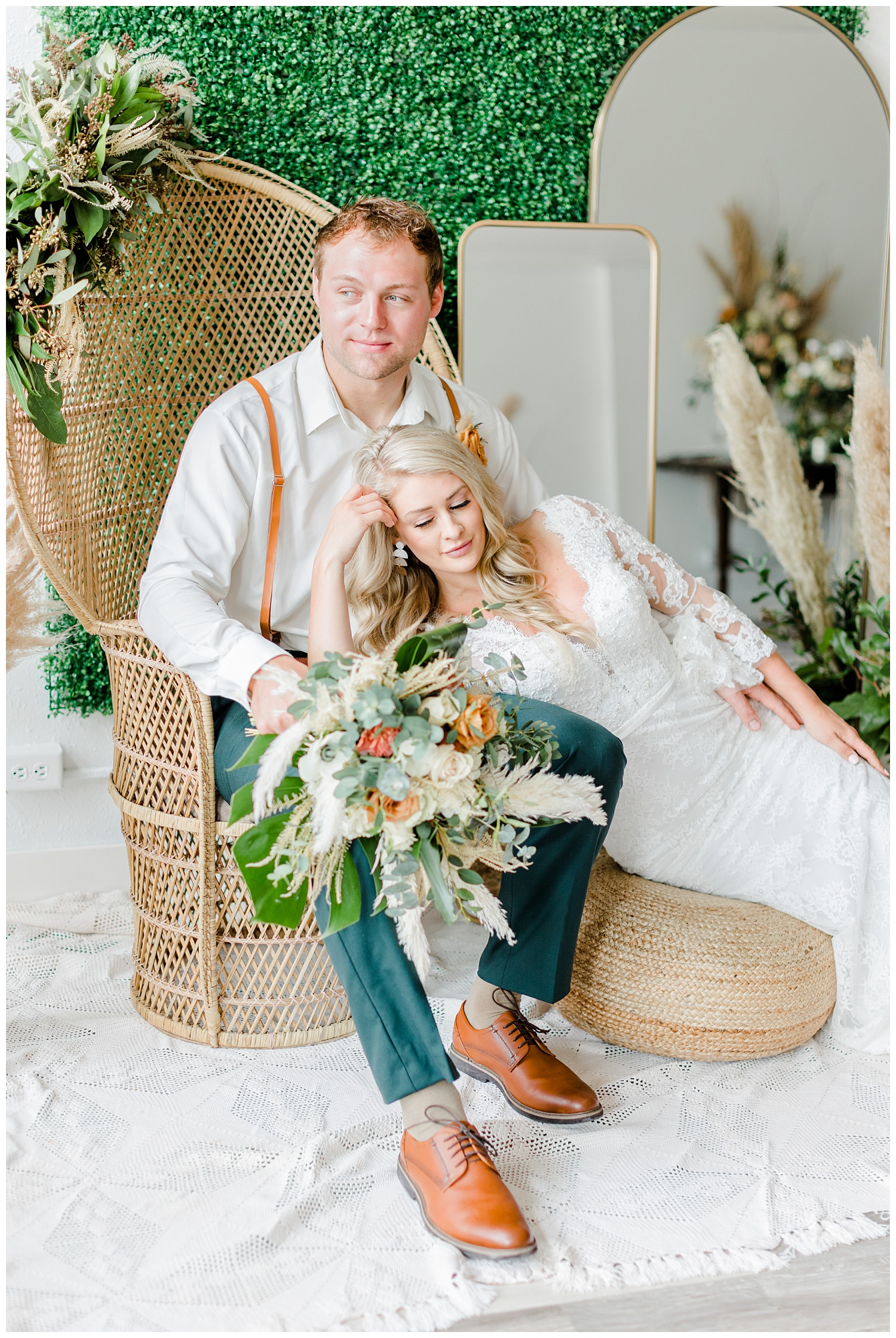 Boho groom sits in a vintage wicker peacock chair with his bride draped in his lap | CB Studio