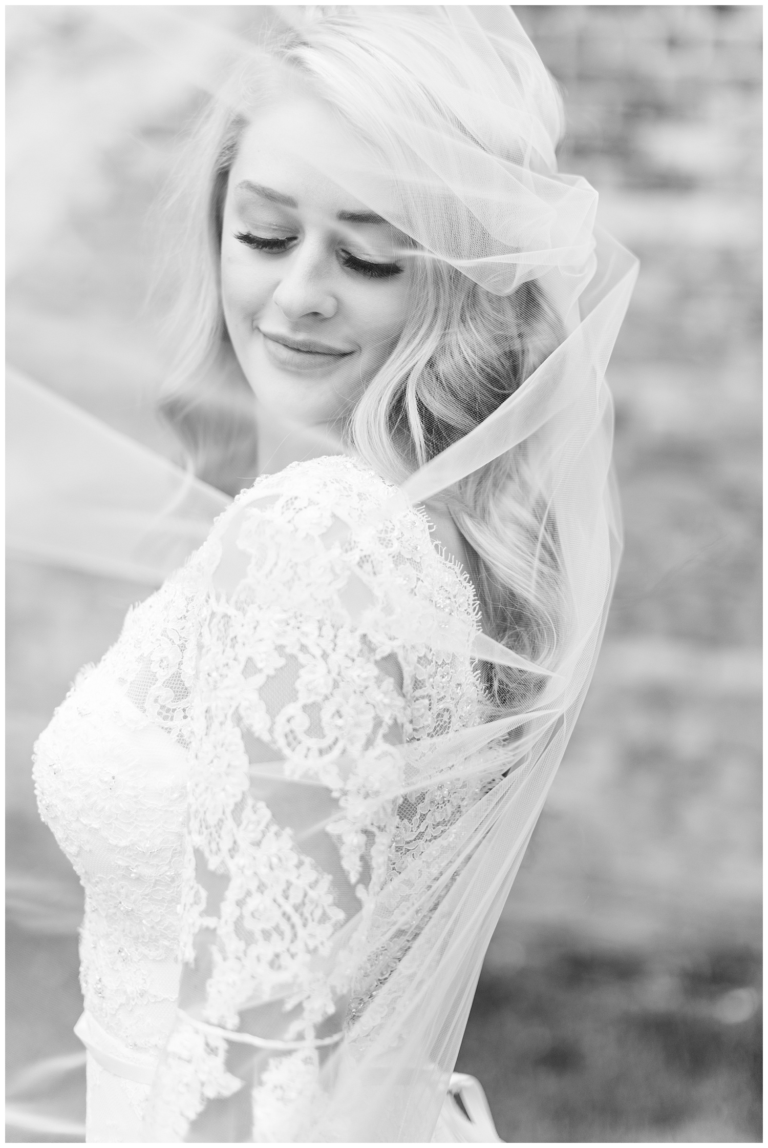 Beautiful bride looks down as her veil blows in the wind | CB Studio