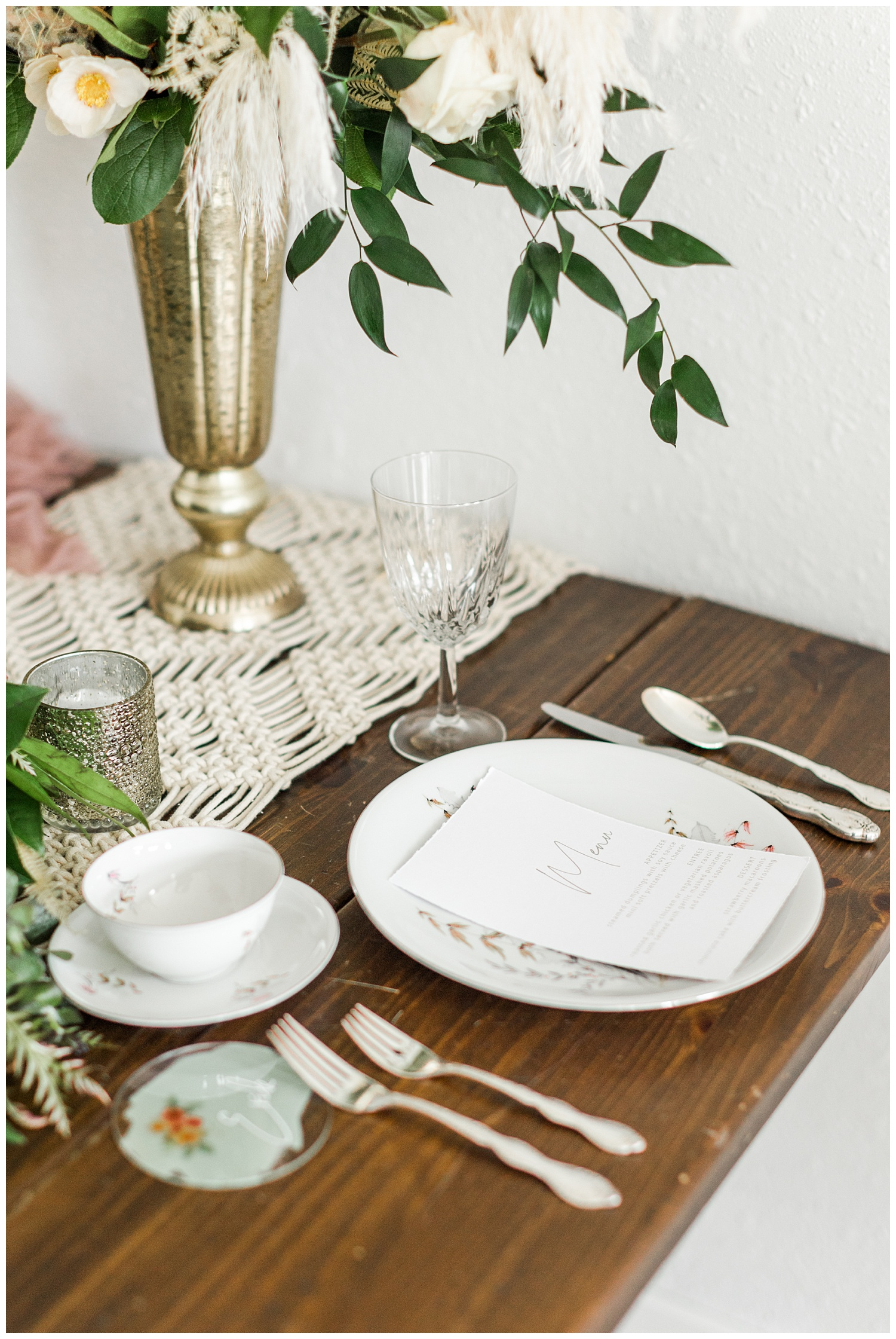 Vintage blush wedding place setting complete with boho florals, macrame and eucalyptus table runner and antique china | CB Studio