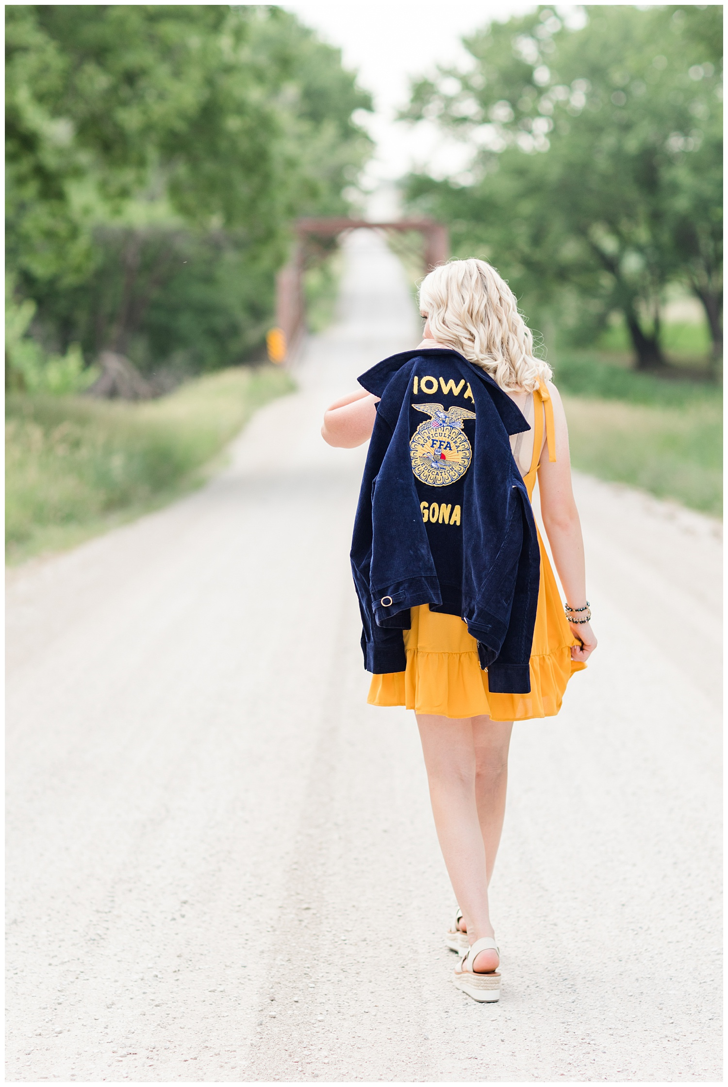 Senior girl Molly walks away on a gravel road with her FFA jacket over her shoulder   CB Studio
