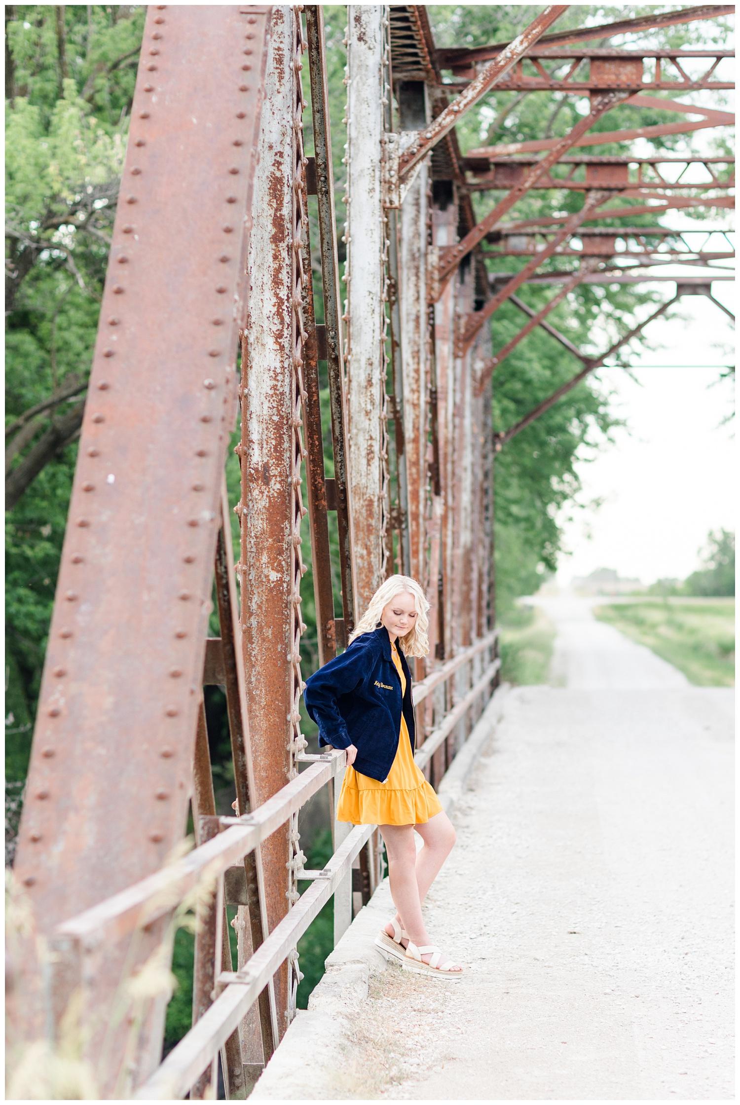 Senior girl Molly wearing her FFA jacket leaning against an old trussle bridge   CB Studio