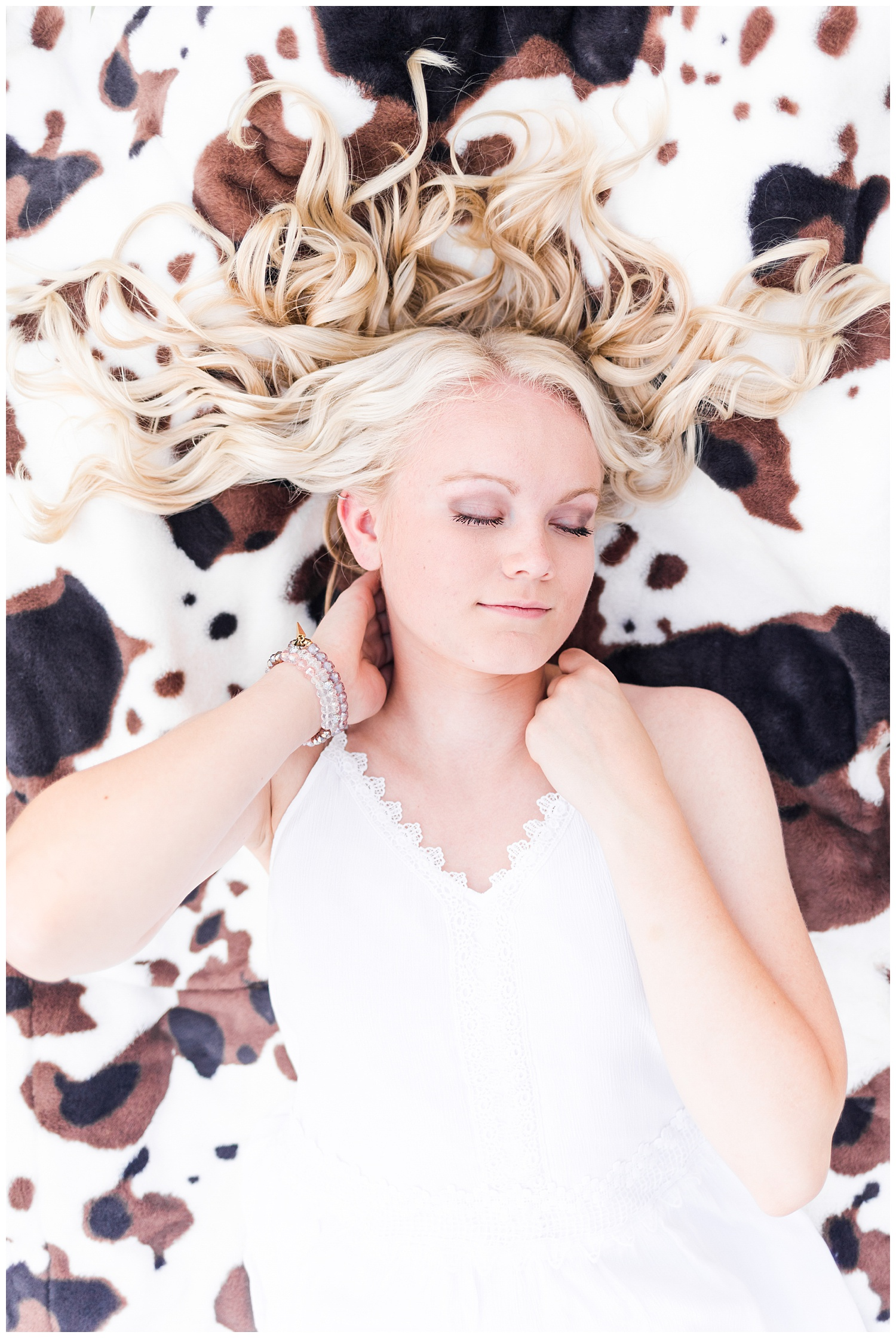 Senior girl Molly laying on a cow print blanket   CB Studio