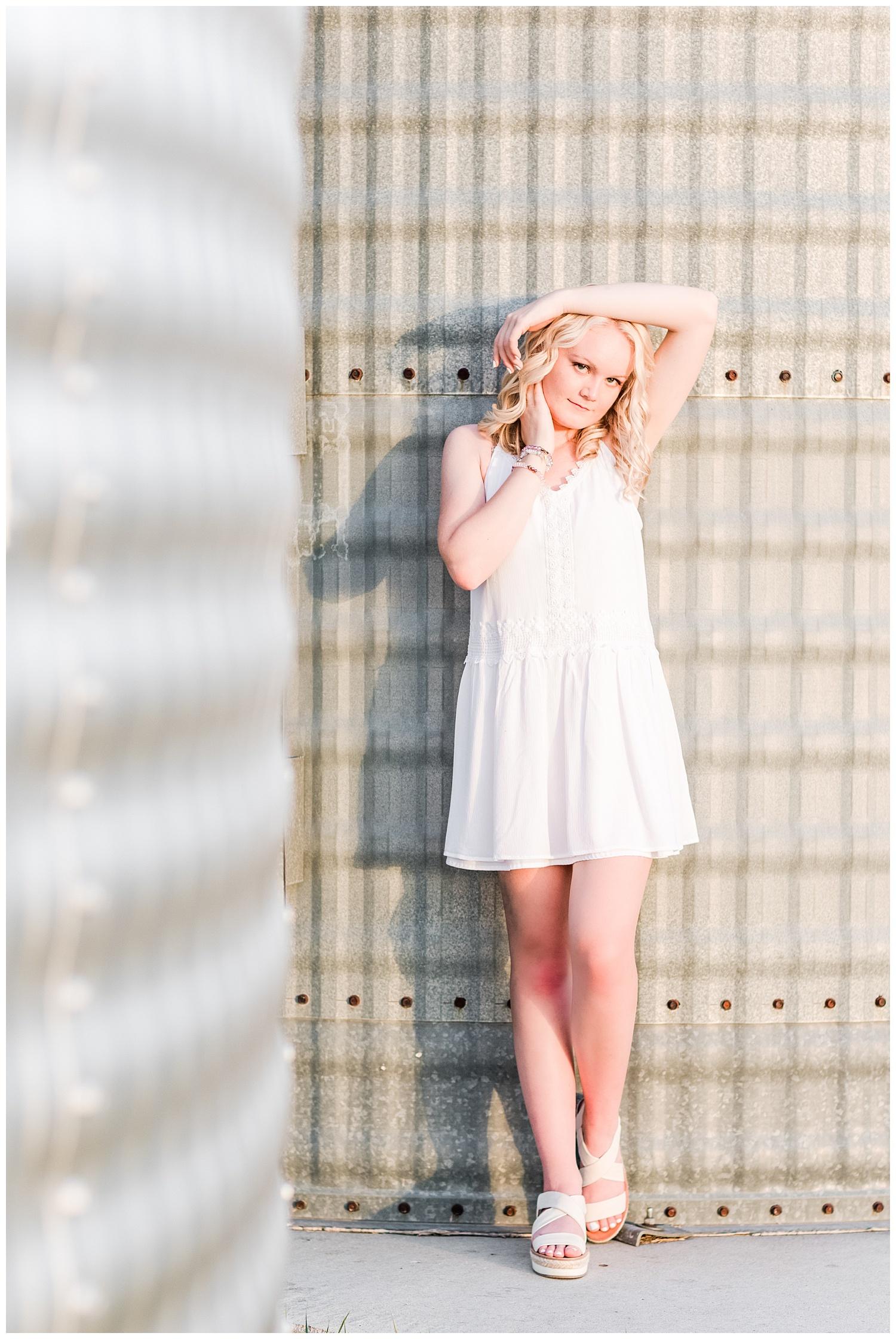 Senior girl Molly wearing a white dress leaning against a grain bin   CB Studio