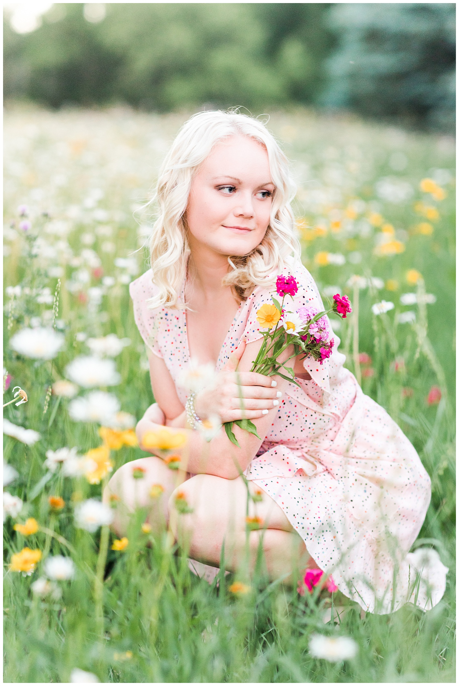 Senior girl Molly in a flower field holding a bouquet of wildflowers   CB Studio