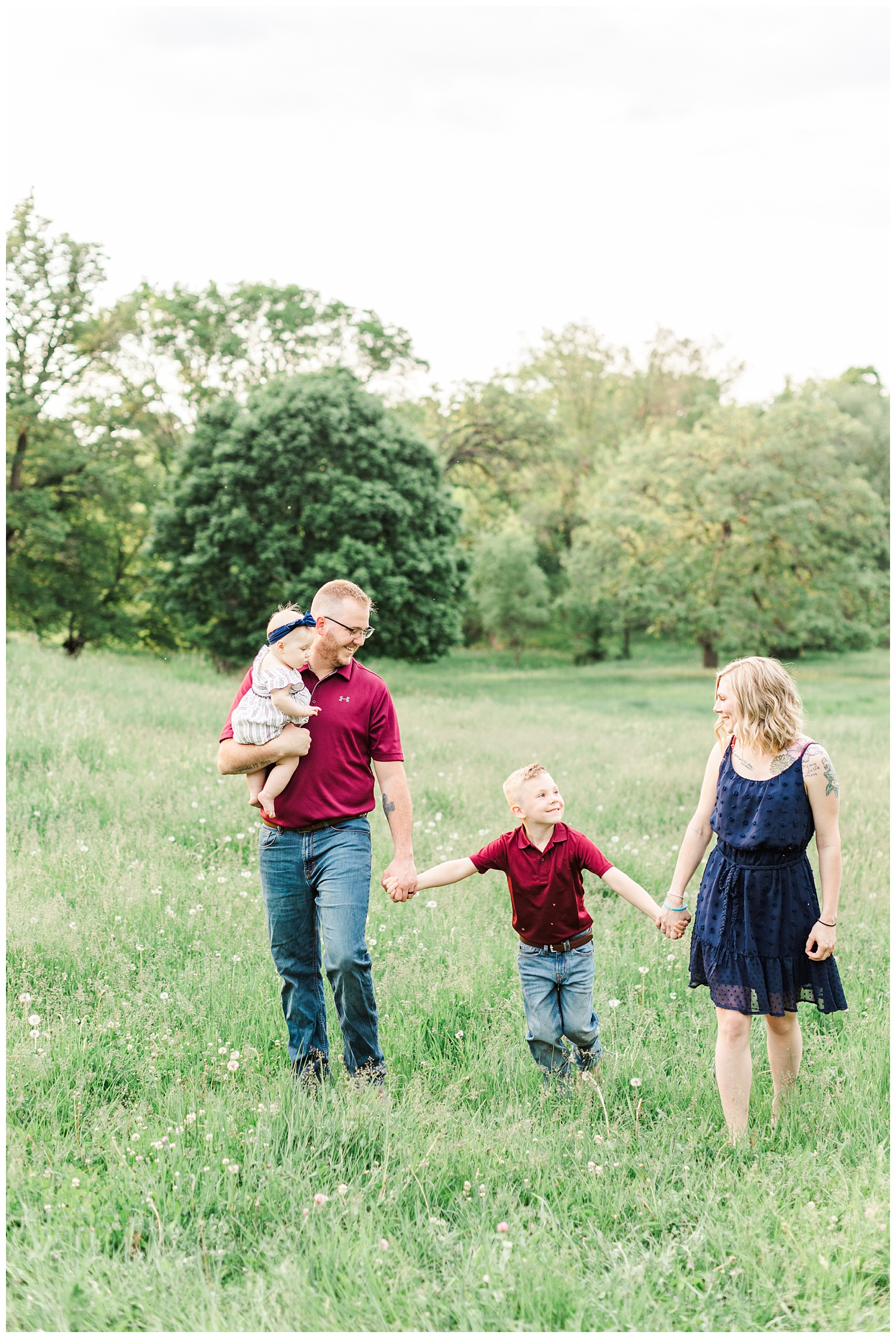 Family walks hand in hand in a grassy pasture with rolling hills in Iowa | CB Studio