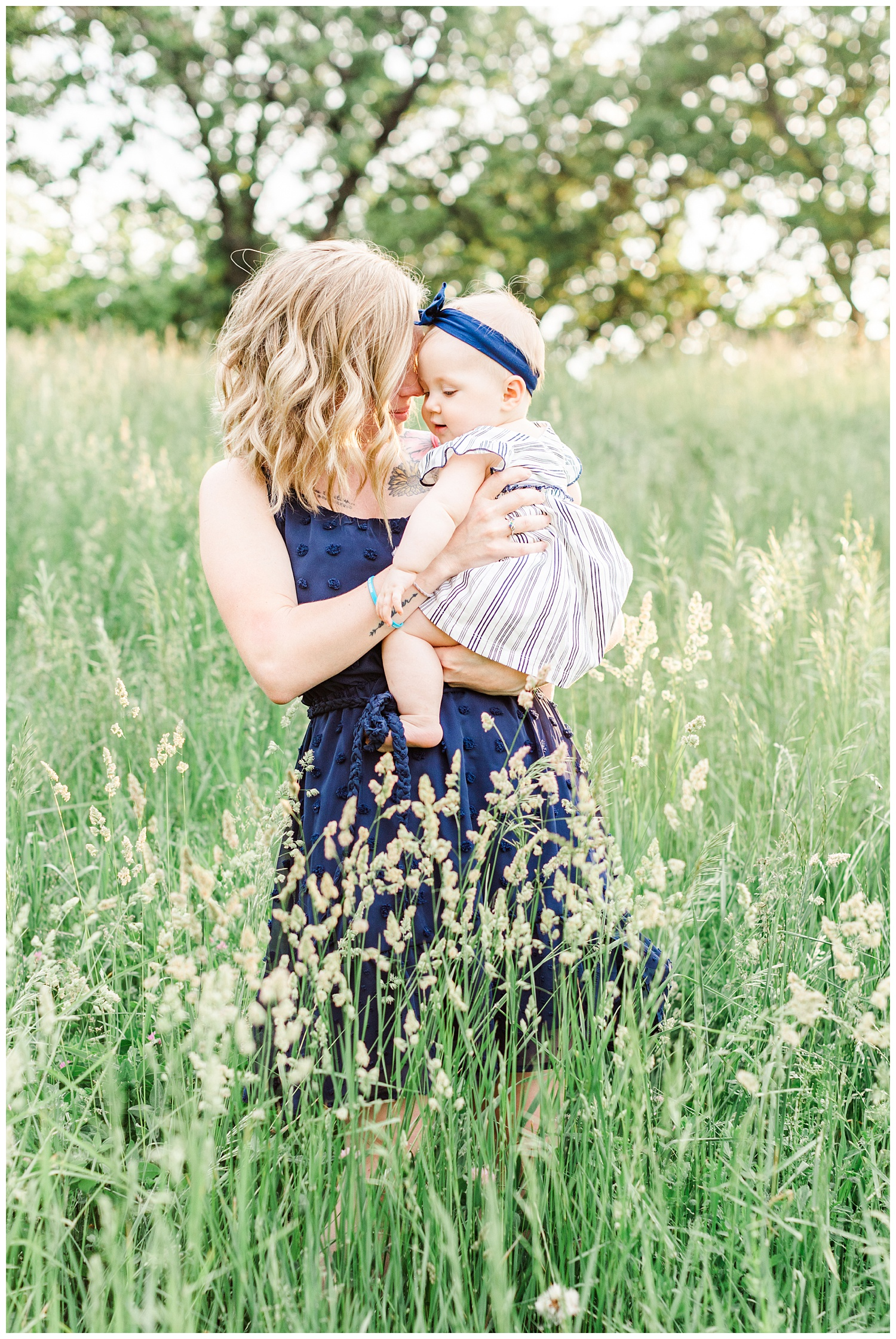 Mama embraces her baby girl at holden hour in a grassy field in Iowa | CB Studio