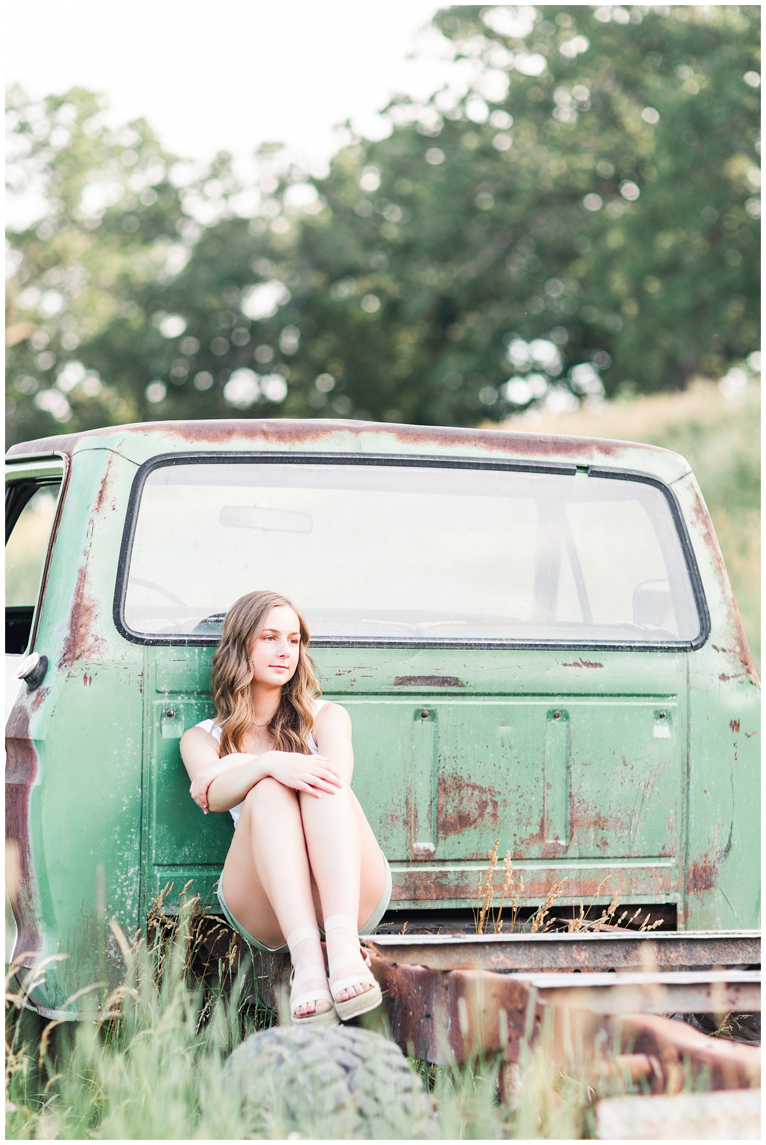 Senior Taylor sitting in the back of an old green Ford truck in a grassy field | CB Studio