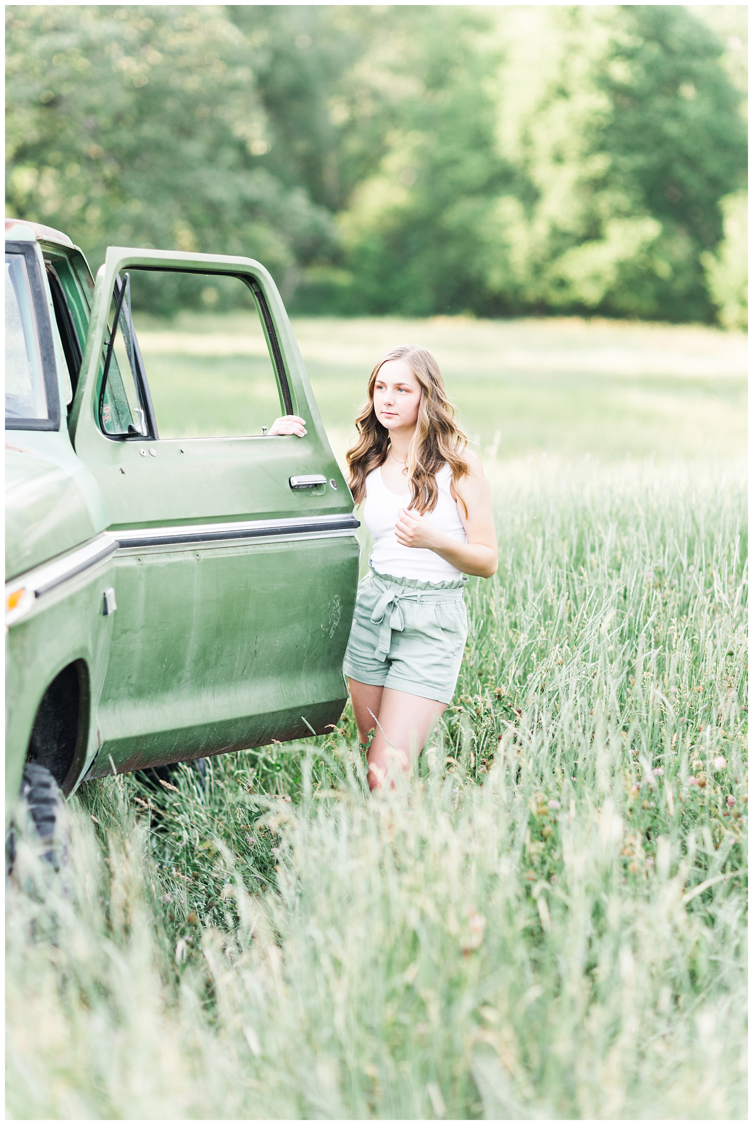Senior Taylor standing next to an old green Ford truck in a grassy field | CB Studio
