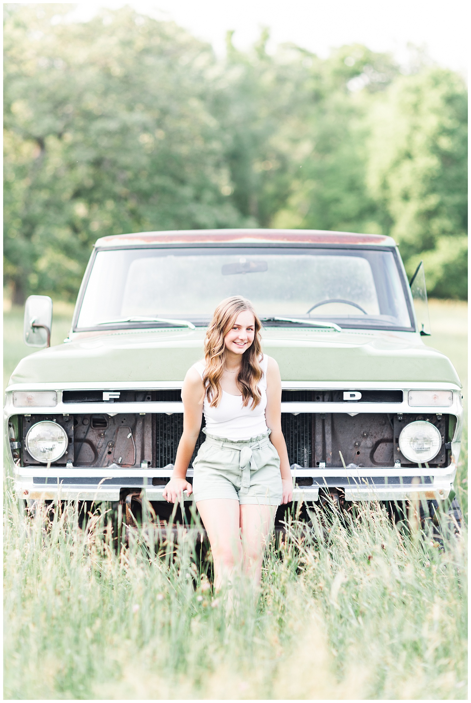 Senior Taylor leaning against an old green Ford truck in a grassy field | CB Studio