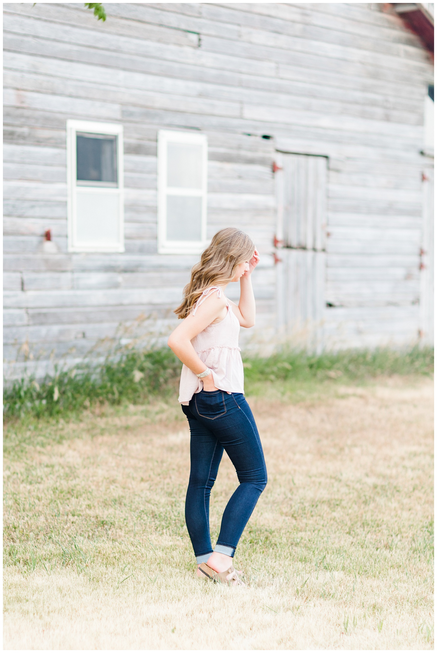 Senior Taylor brushes her hair aside as the wind blows with an old wooden barn in the background | CB Studio