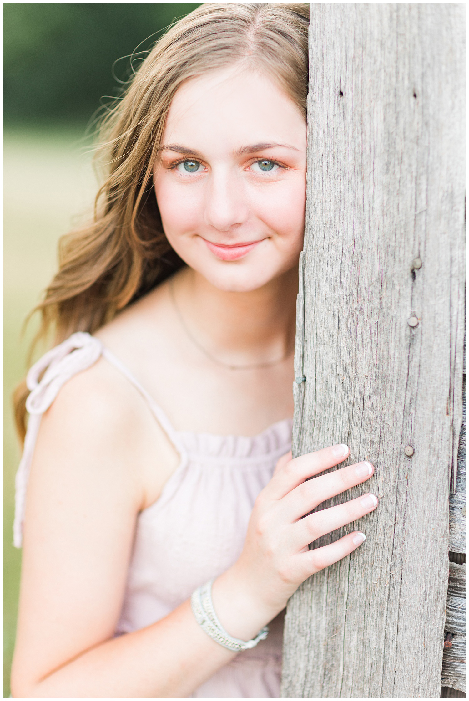 Senior Taylor smiles softly as she leans against an old wood barn | CB Studio