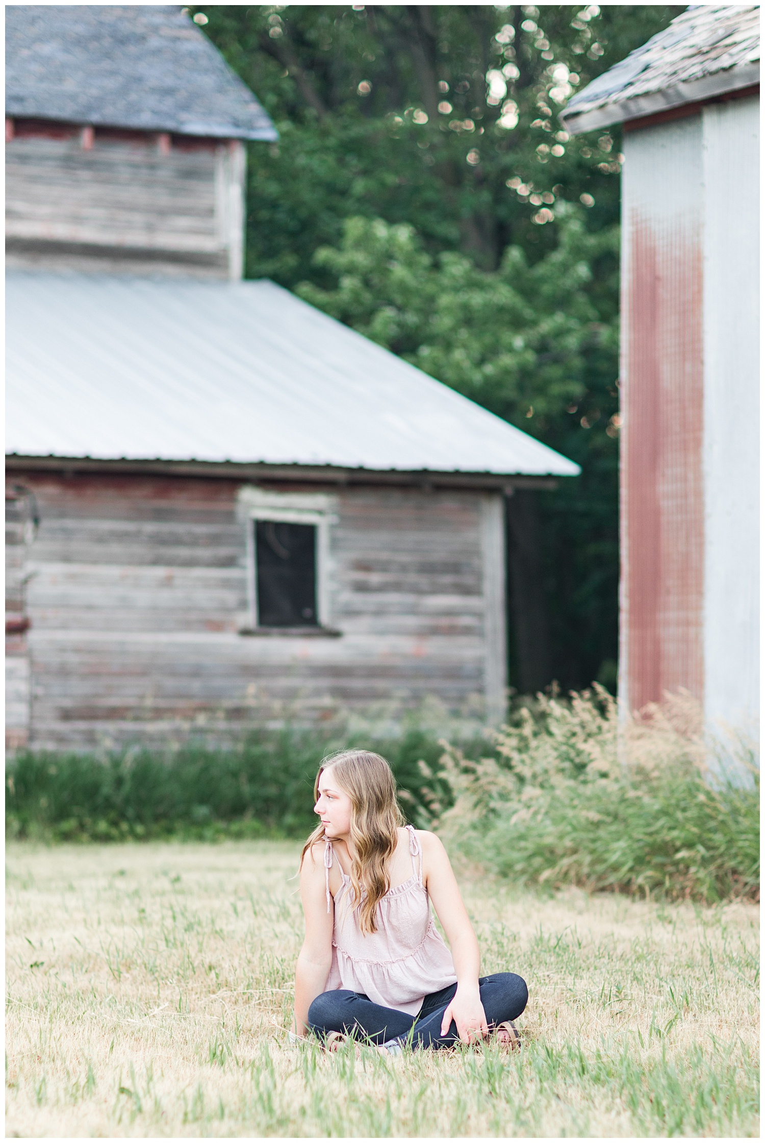 Senior Taylor sits in the grass with some old wood barns in the background | CB Studio