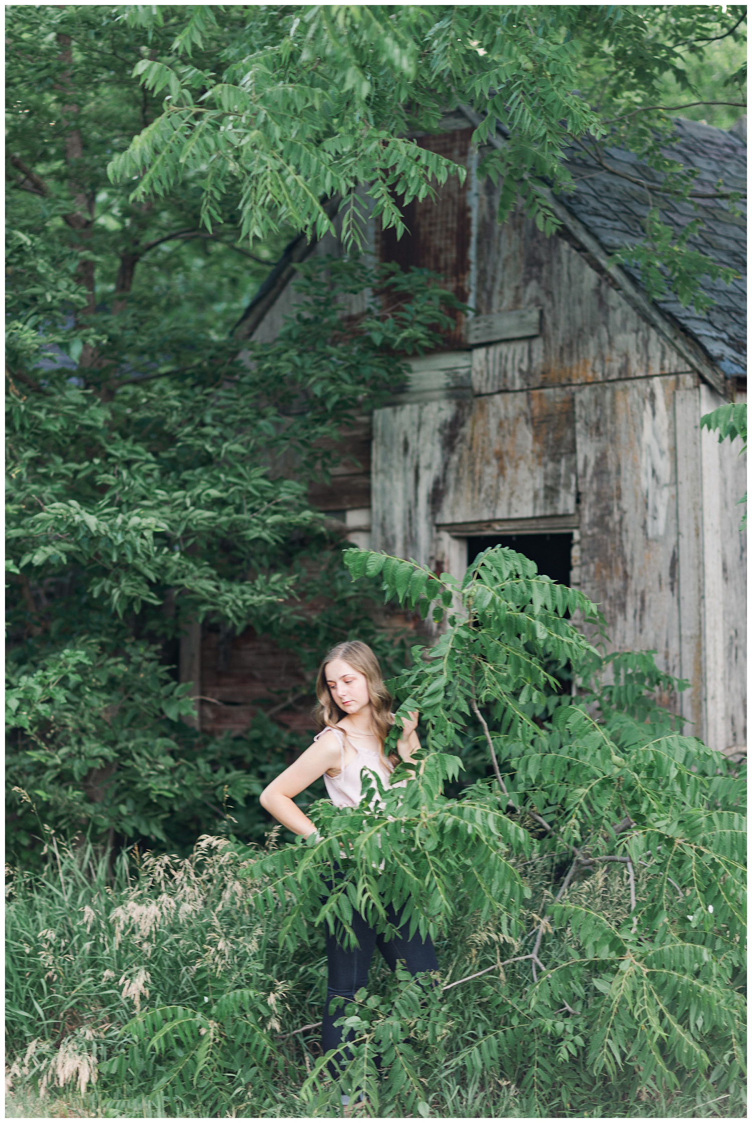 Senior Taylor looks down as she is surrounded by green foliage with a wood barn in the background | CB Studio