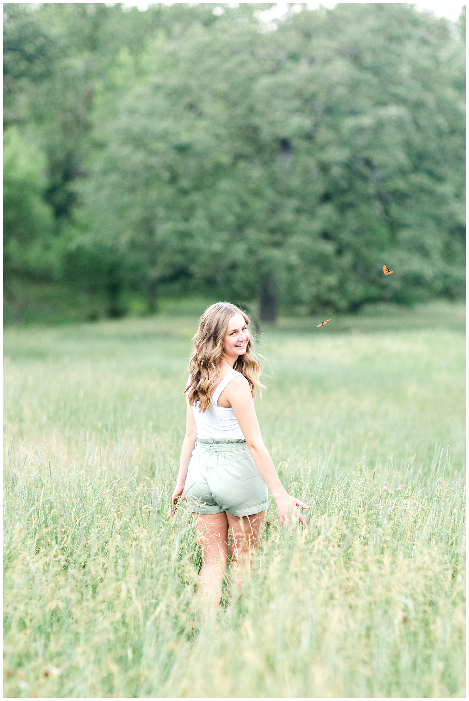 Senior Taylor walking away in a grassy field with butterflies flying around her | CB Studio