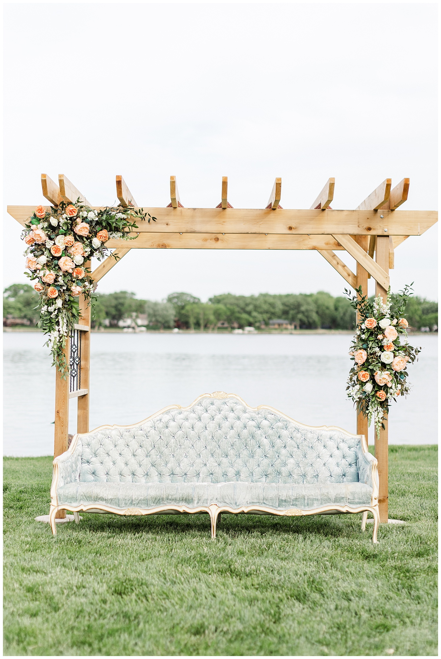 Wedding arch adorned with peach garden roses and accompanied by a dusty blue victorian couch with a beautiful lake background | CB Studio