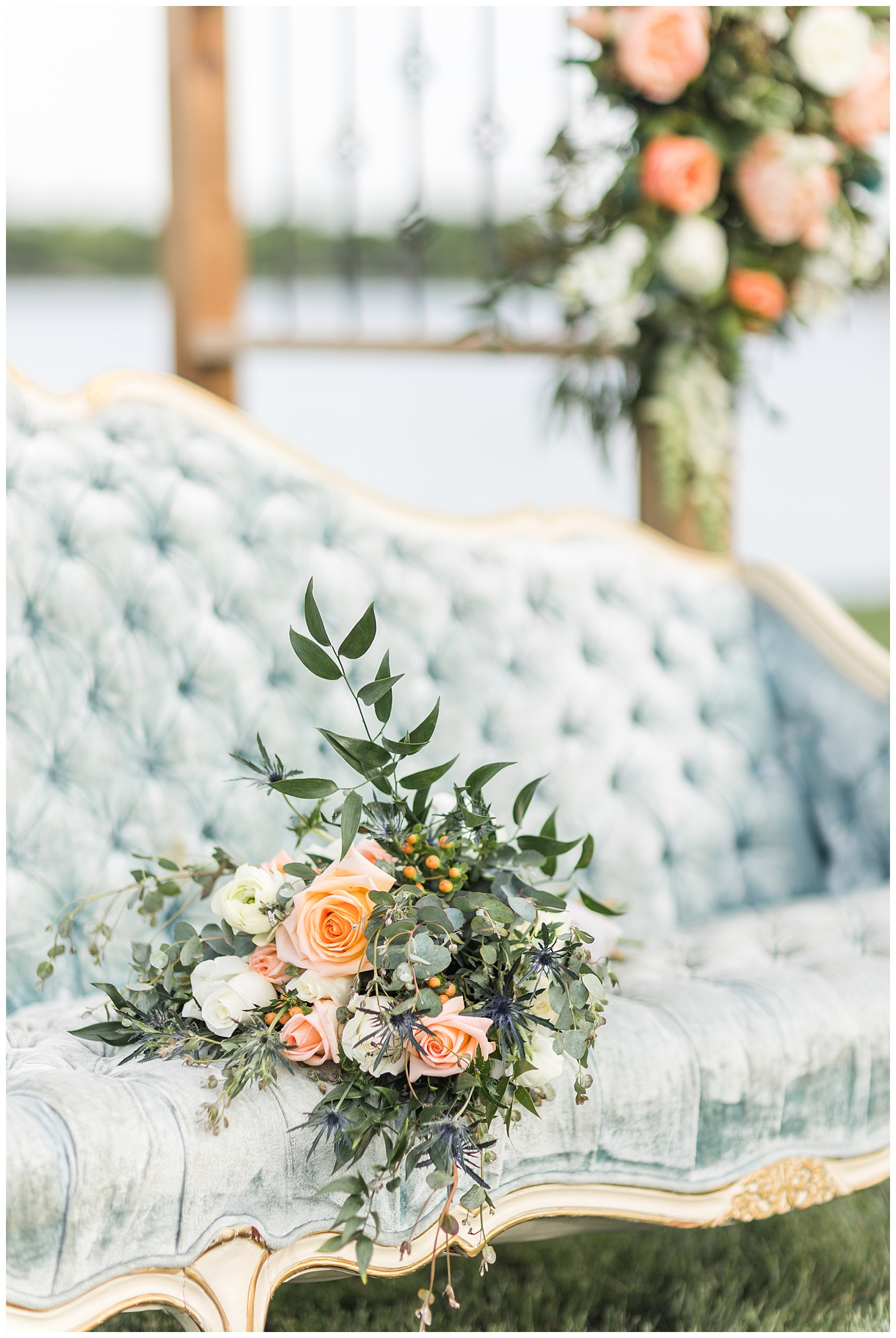 Peach and white rose wedding bouquet with white ranunculus and eucalyptus sitting on top of a dusty blue victorian couch | CB Studio