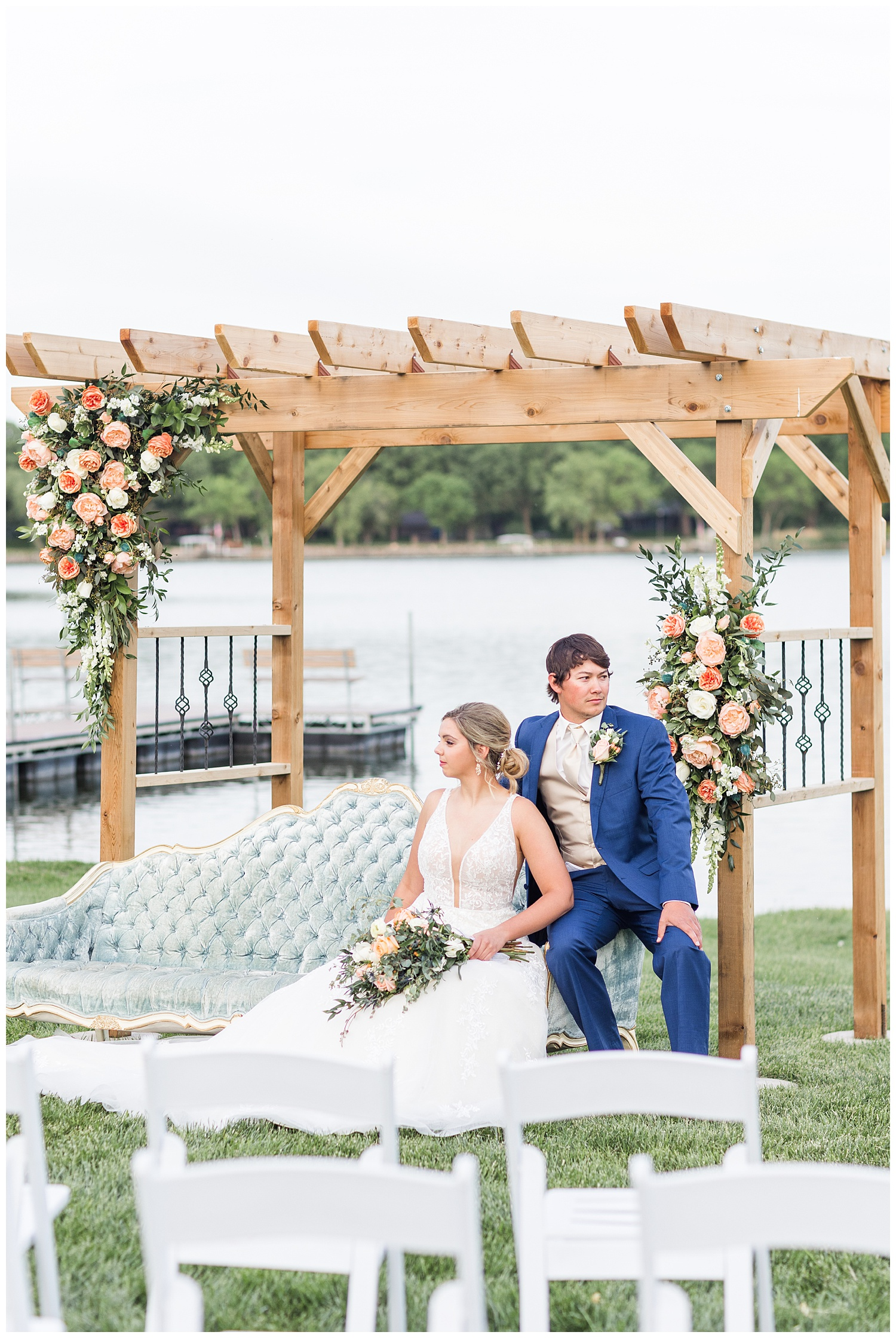 Bride and groom sit on a dusty blue victorian couch under a wooden wedding arch adorned with peach garden roses | CB Studio