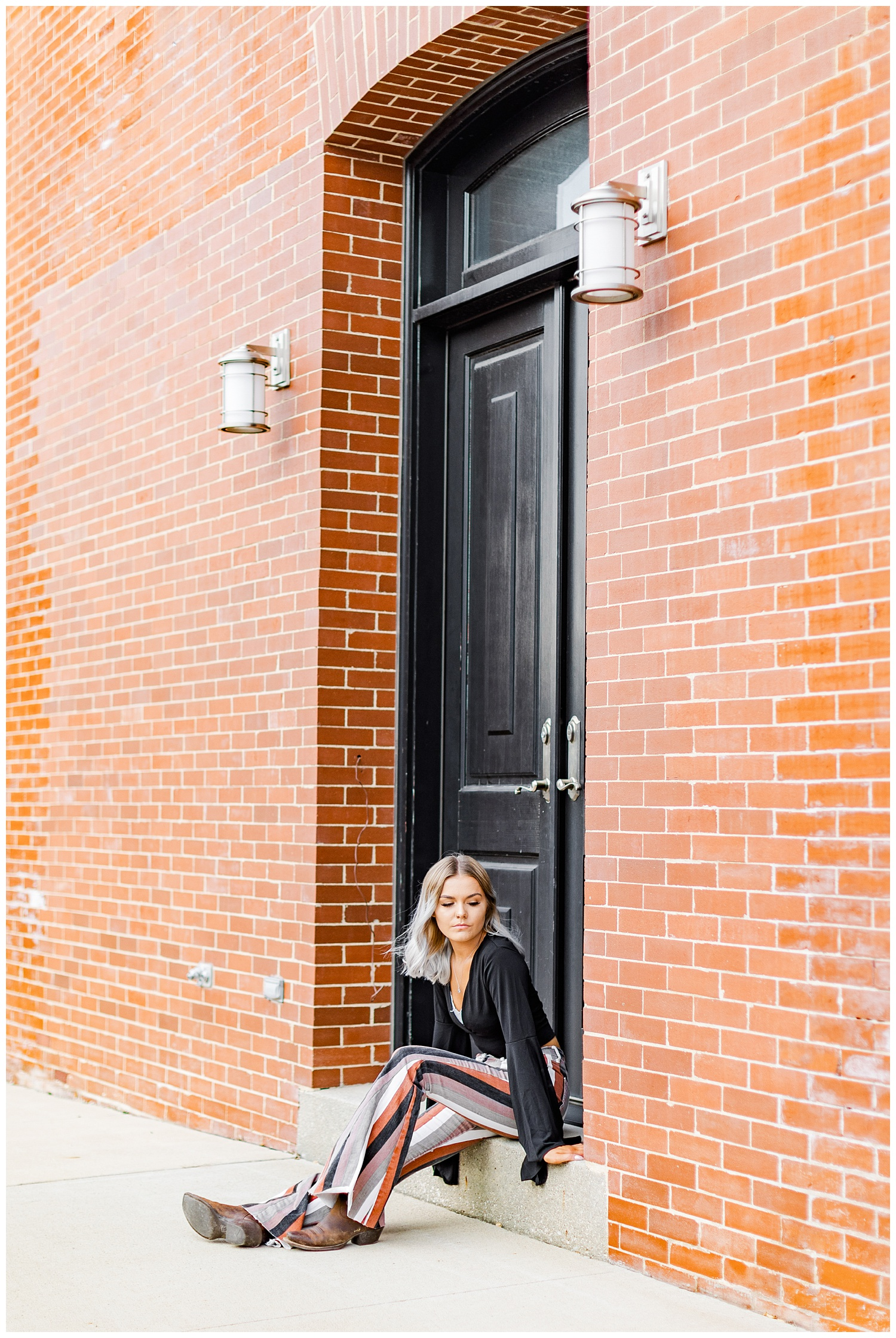 Addison dressed in boho style sits on a door step in downtown Algona, IA   CB Studio