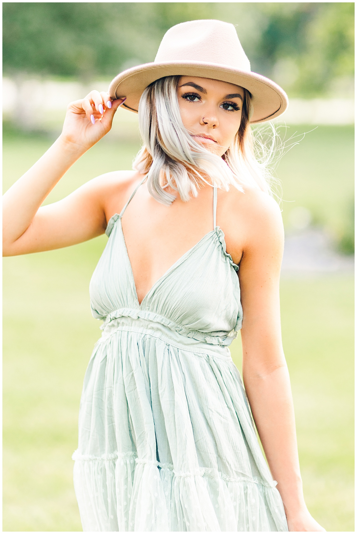 Addison wearing a green dress holds the brim of her hat while her hair blows in the breeze   CB Studio