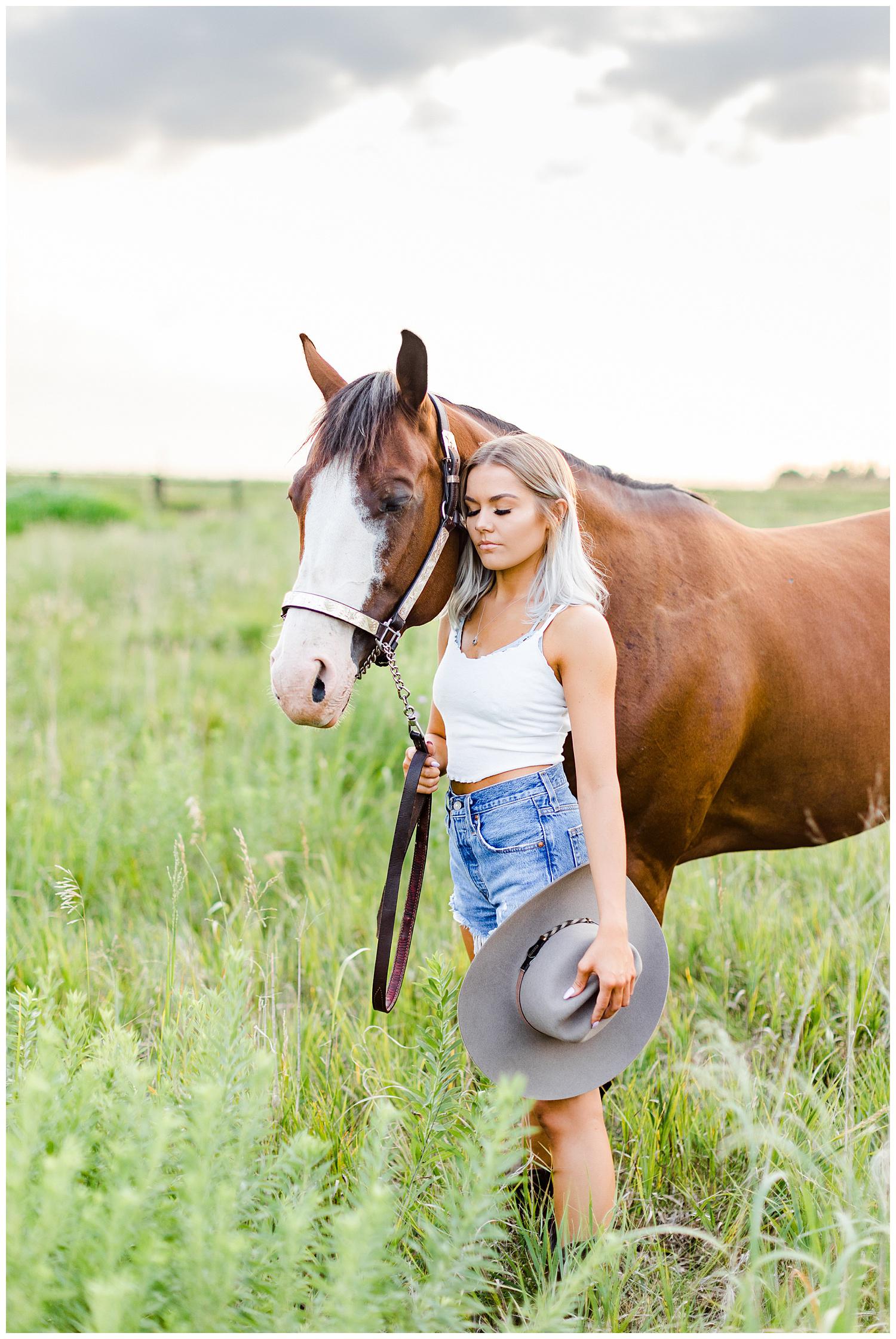 Addison snuggles Miss Flirty the horse in a grassy field   CB Studio