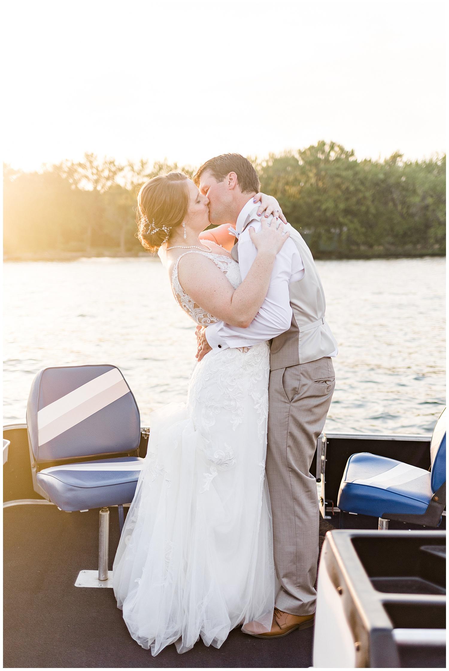 Chris and Hannah share a kiss during sunset on a pontoon on East Okoboji Lake on their wedding day | CB Studio