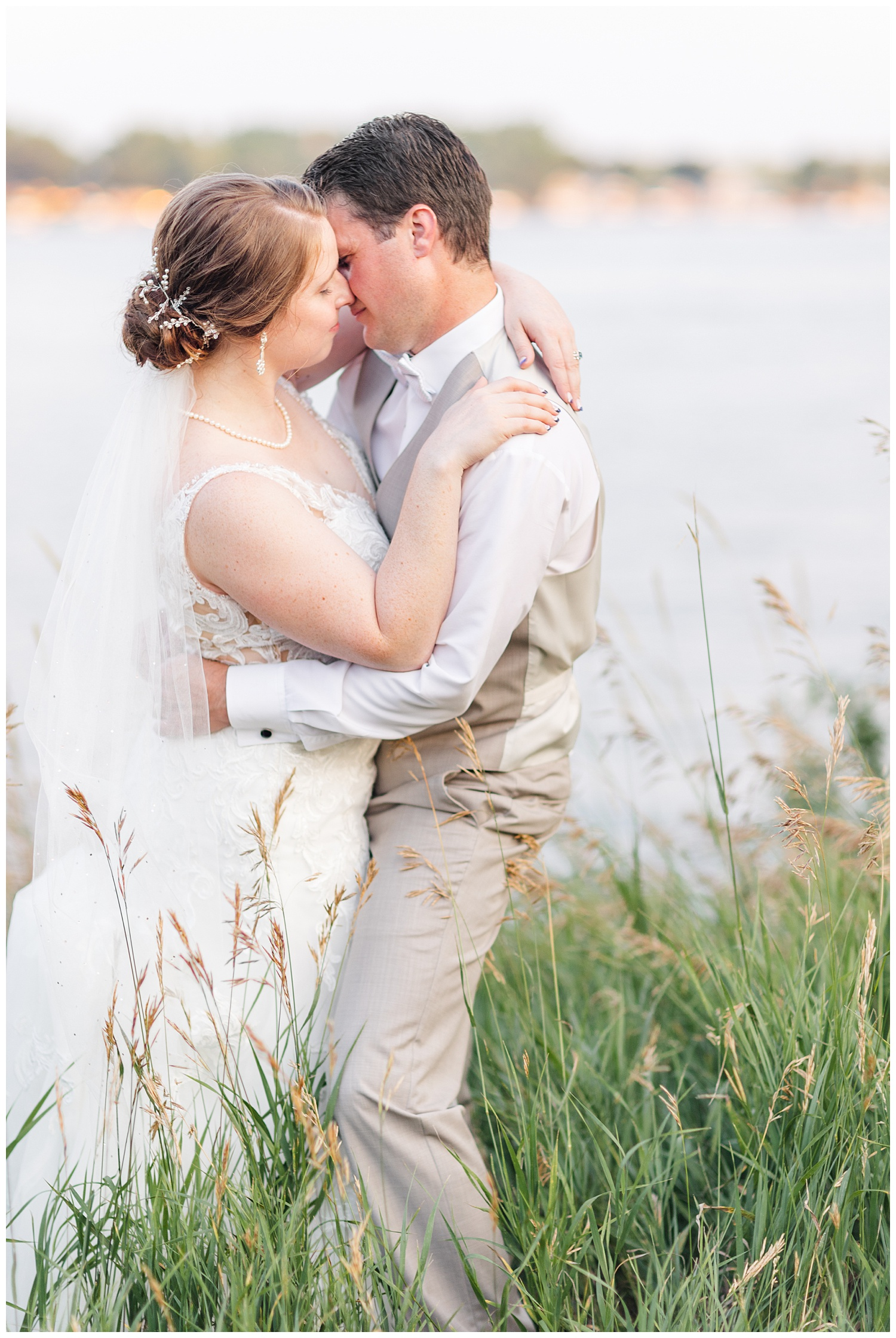 Chris and Hannah embrace in front of East Okoboji Lake on their wedding day | CB Studio