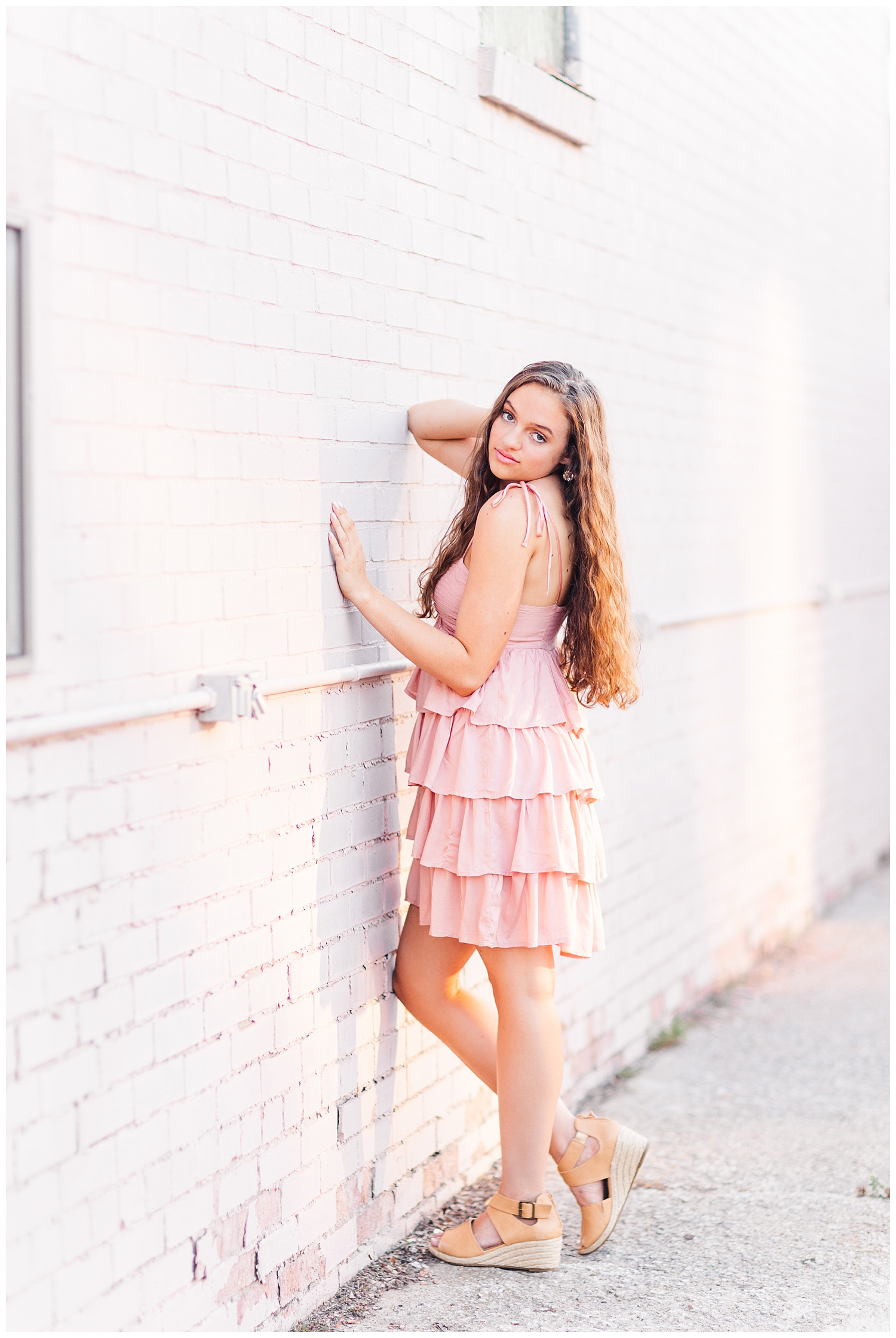 Senior Kennedy leans against a pink block wall in downtown Fort Dodge   CB Studio