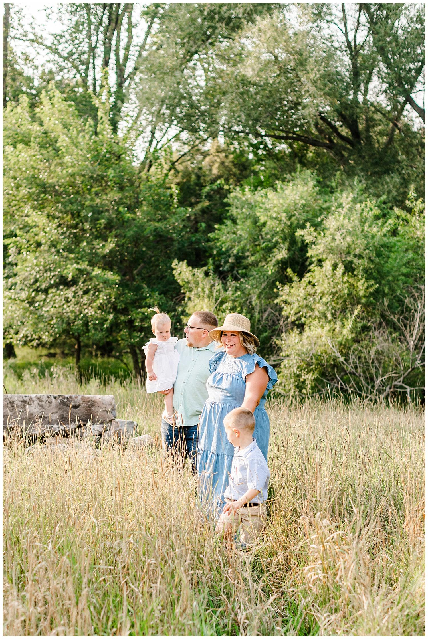 The Bruhn family walk together in a grassy pasture in Iowa | CB Studio