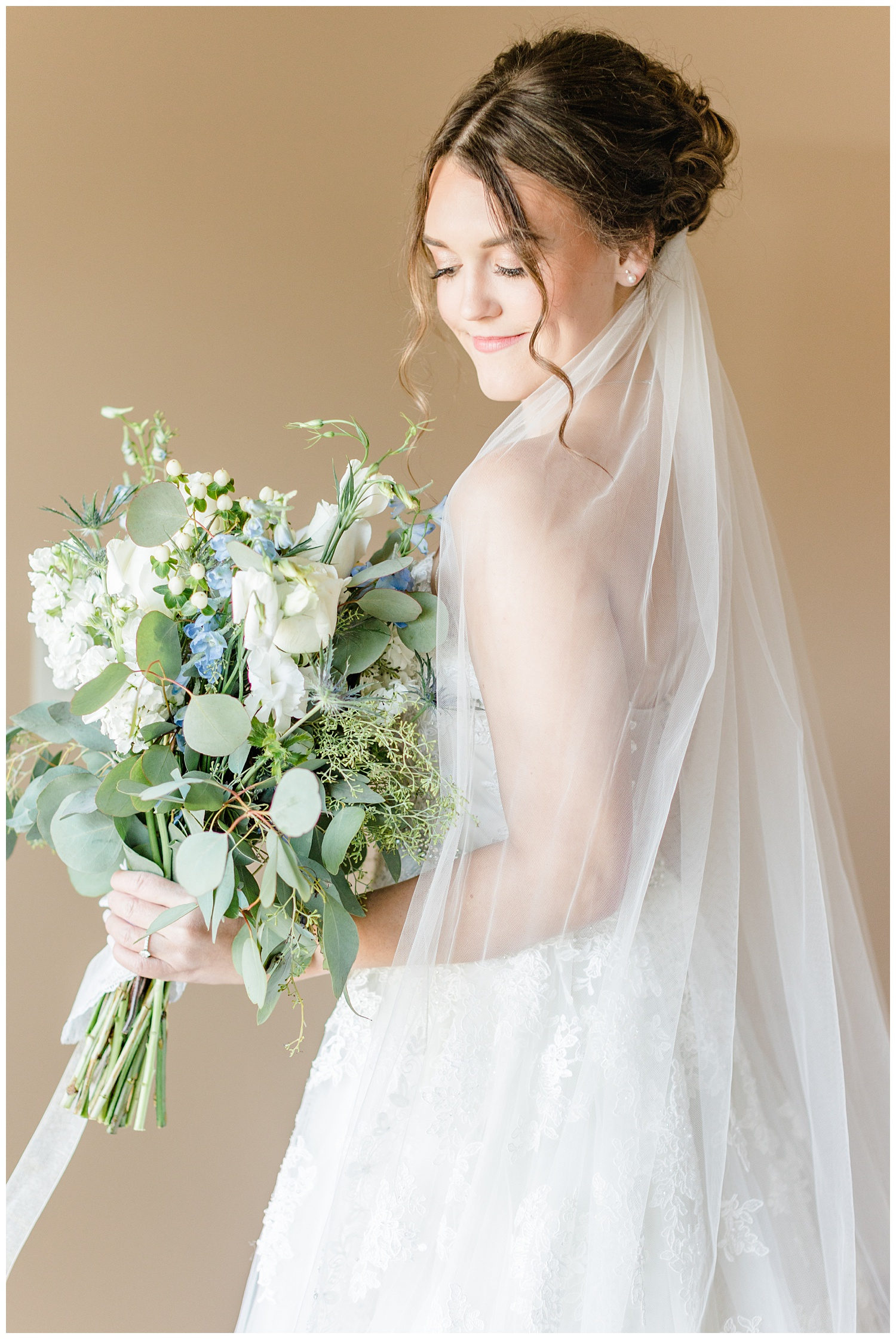 Bride Jenna wearing Sophia Tolli and holding her loose gathered bouquet of white roses, sea holly, and eucalyptus   CB Studio