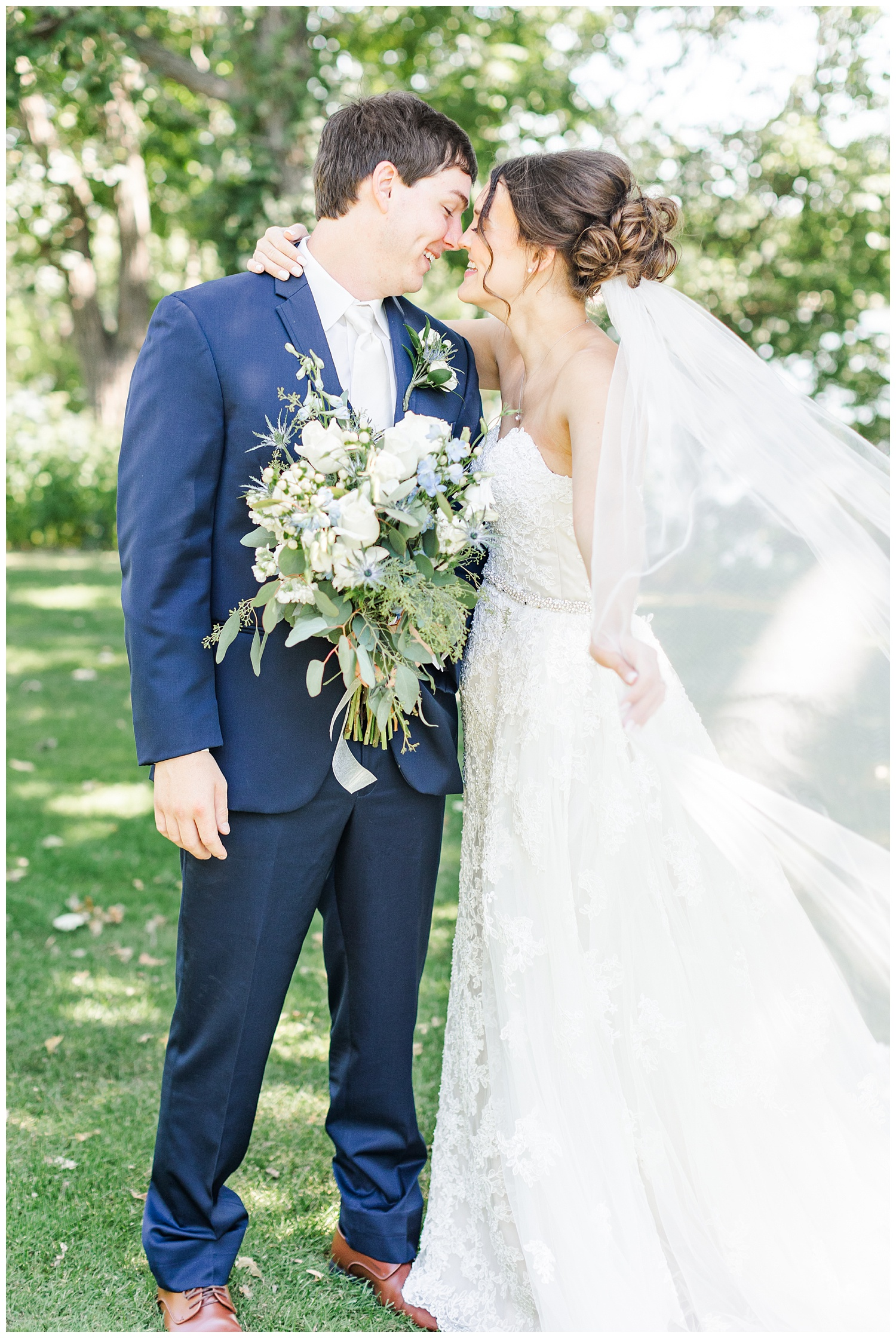 Bride and groom embrace and laugh while her veil blows in the wind   CB Studio