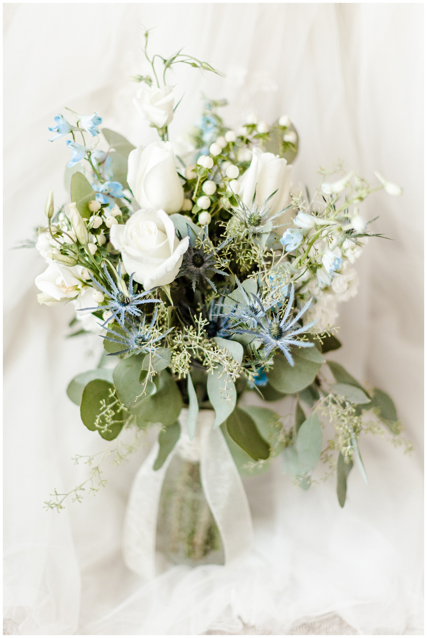 Loose gathered bridal bouquet with white roses, eucalyptus, sea holly and white hypericum berries   CB Studio