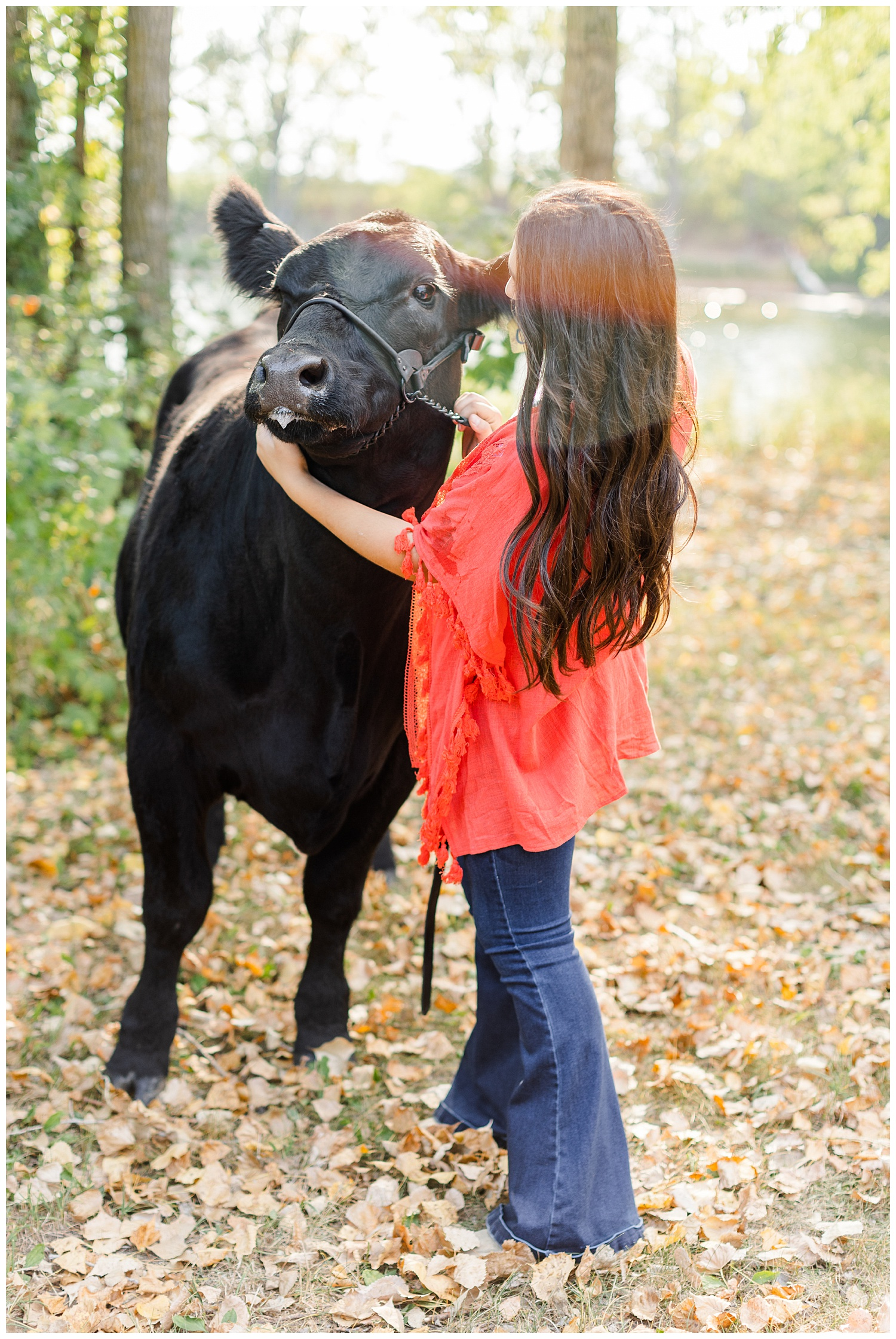 Laney, wearing a coral Kimono, pets her show cow, Queen | CB Studio
