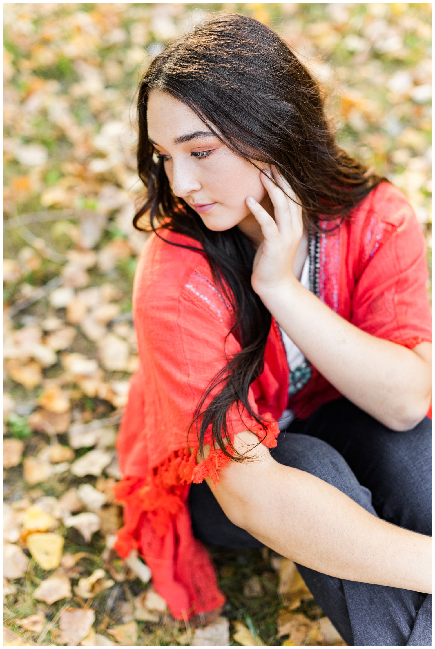Laney, wearing a coral Kimono, looks over her shoulder while sitting on a bed of fall leaves | CB Studio