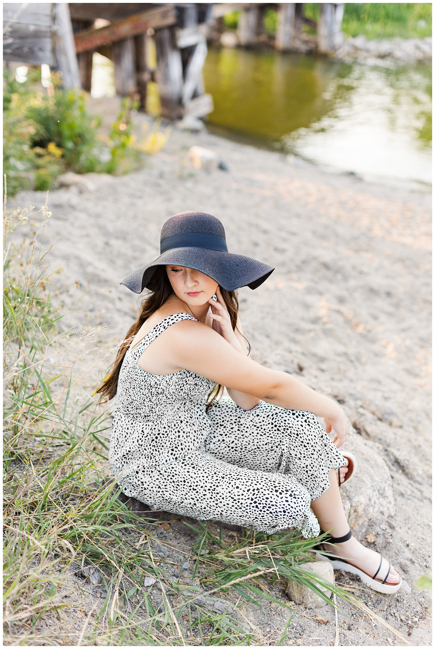Laney wearing a black and white jumpsuit and black sun hat looks over her shoulder while sitting on the shores of Five Island Lake in Emmetsburg | CB Studio