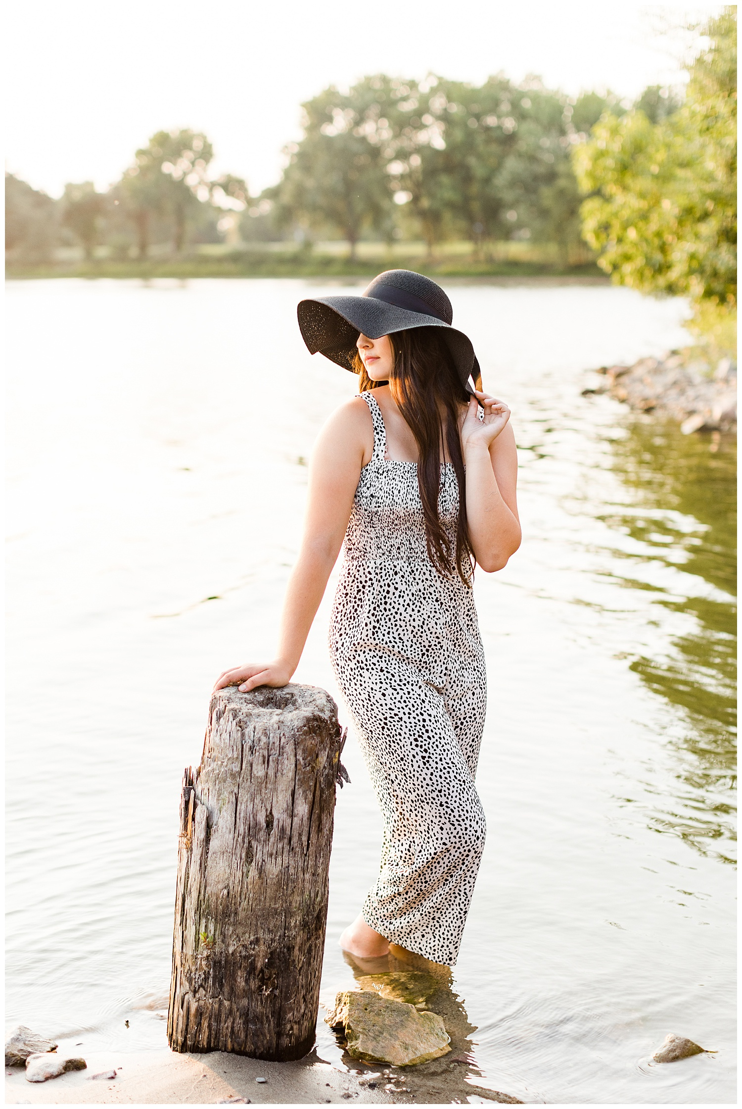 Laney wearing a black and white jumpsuit and black sun hat looks over her shoulder while standing in the water of Five Island Lake in Emmetsburg | CB Studio