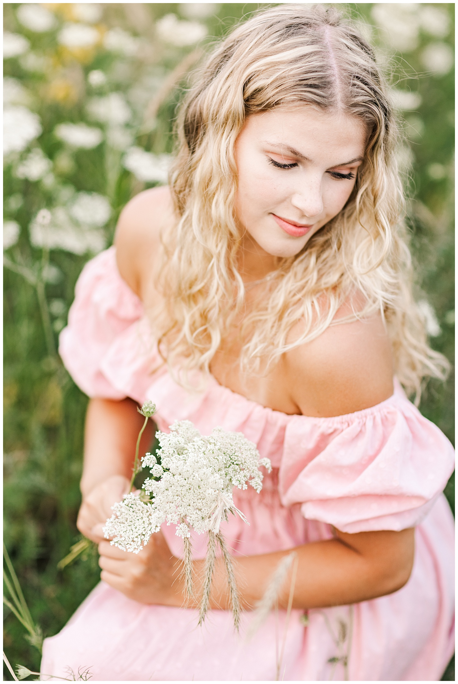Senior Rachel wearing a light pink off the shoulder dress crouches down in a wildflower field | CB Studio