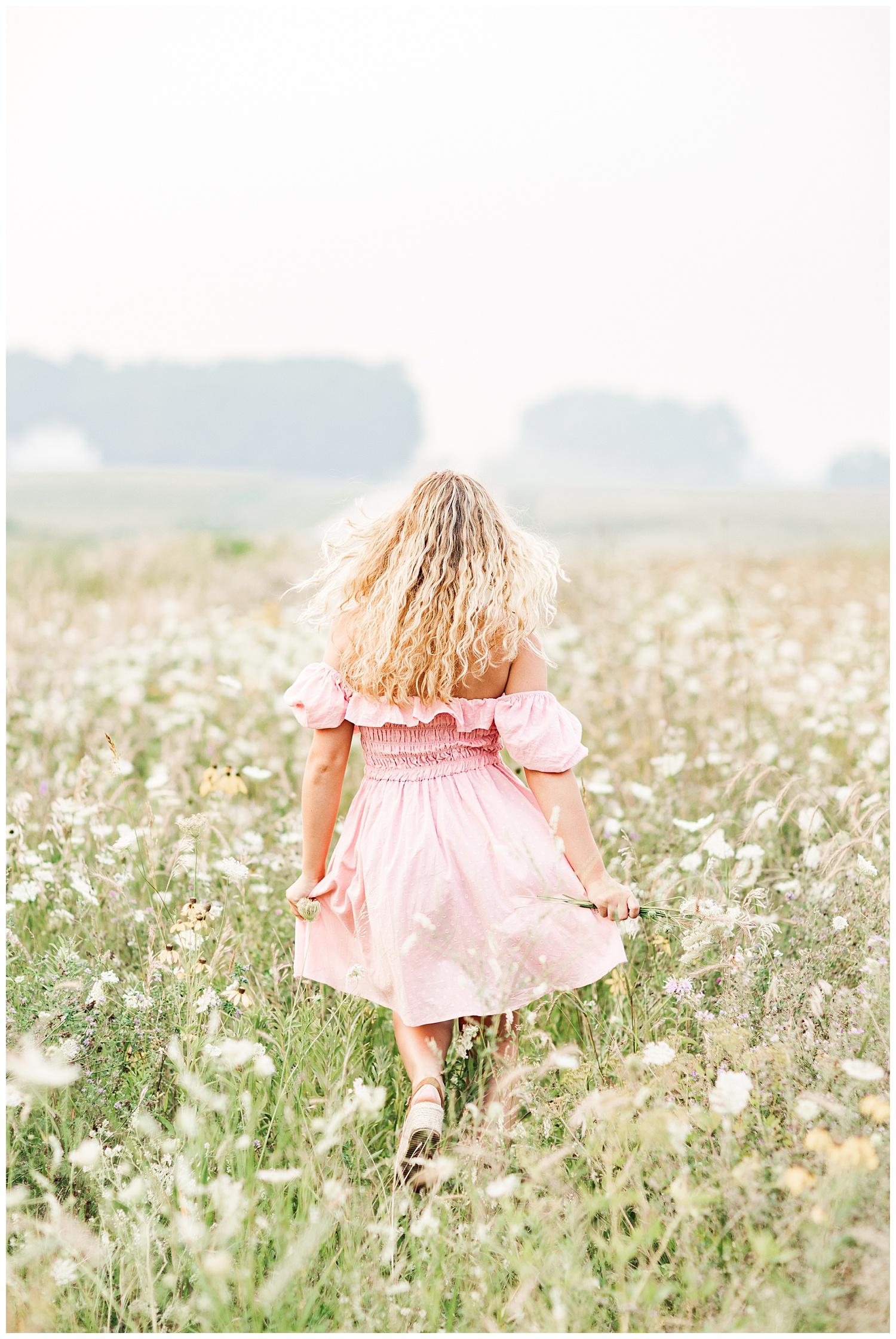 Senior Rachel wearing a light pink off the shoulder dress runs away in a wildflower field | CB Studio