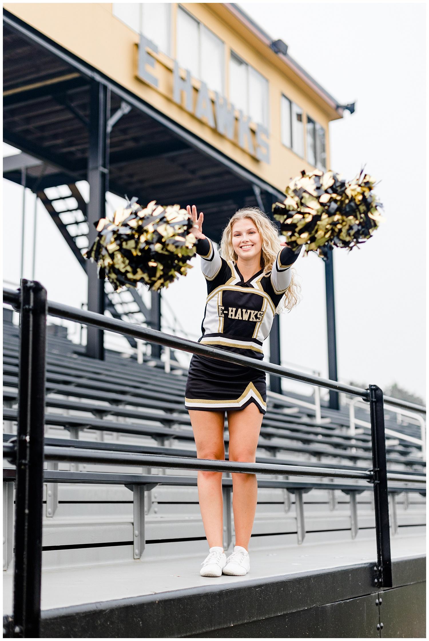 Senior Rachel from Emmetsburg High throws her cheerleading pows forward as she stands on the bleachers in the football field | CB Studio