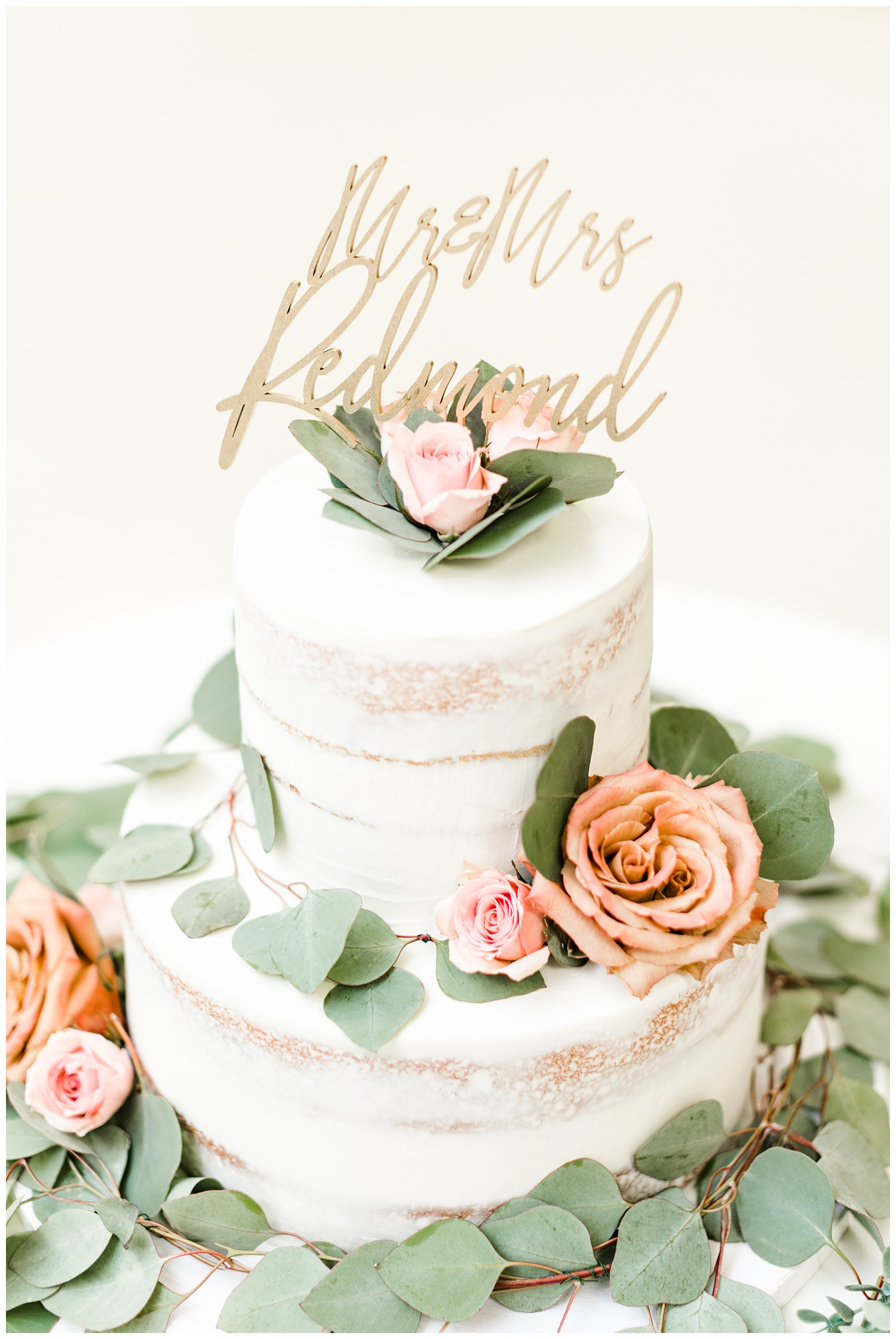 Naked wedding cake adorned with light pink and dusty orange roses as well as eucalyptus and a custom Mr. & Mrs. Redmond cake topper   CB Studio
