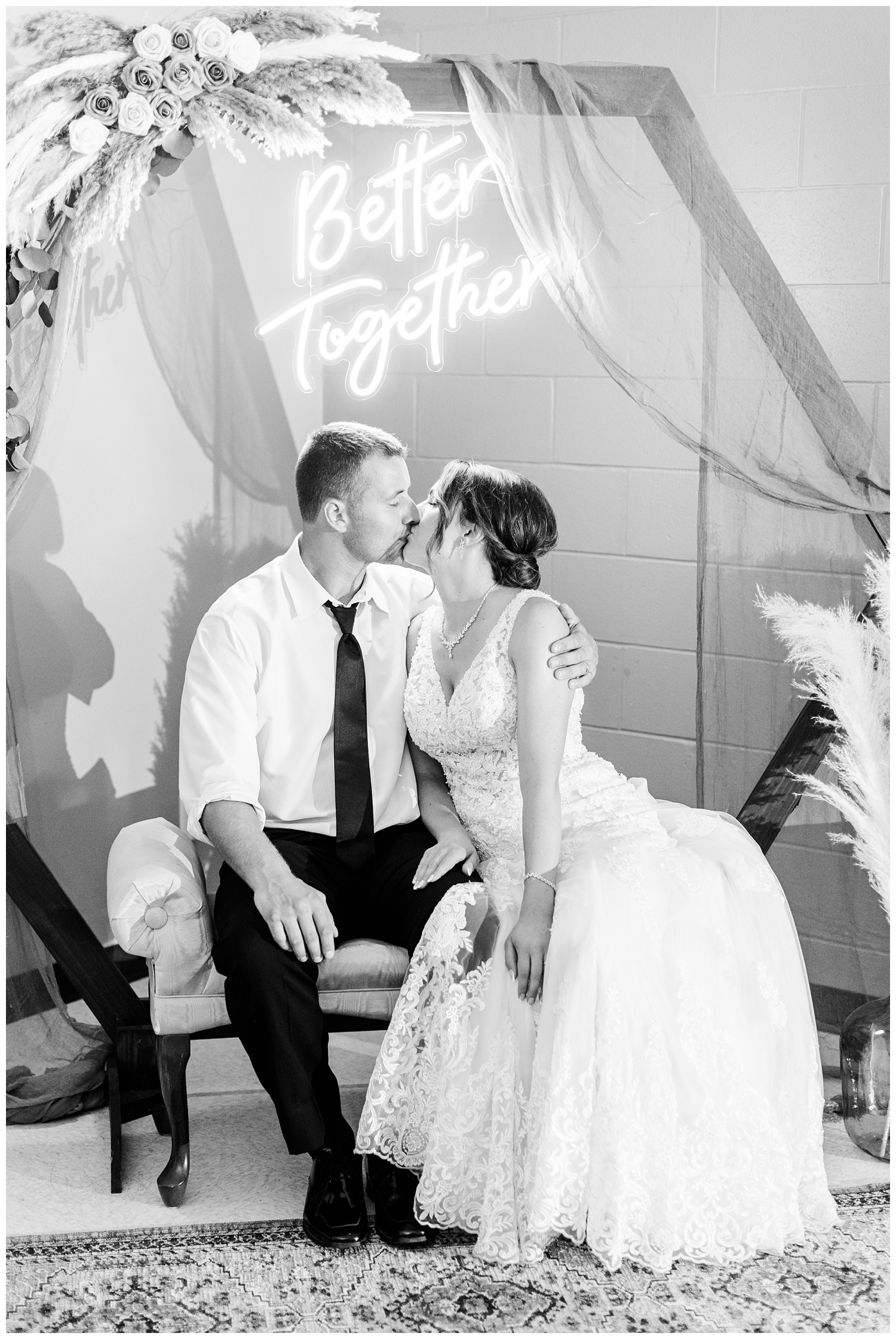 """Mr. & Mrs. Redmond kiss under a custom boho themed photo backdrop featuring a wooden hexagon arch with draping cloths, """"Better Together"""" neon sign, rose and pampas grass arrangements, antique rug and vintage settee   CB Studio"""