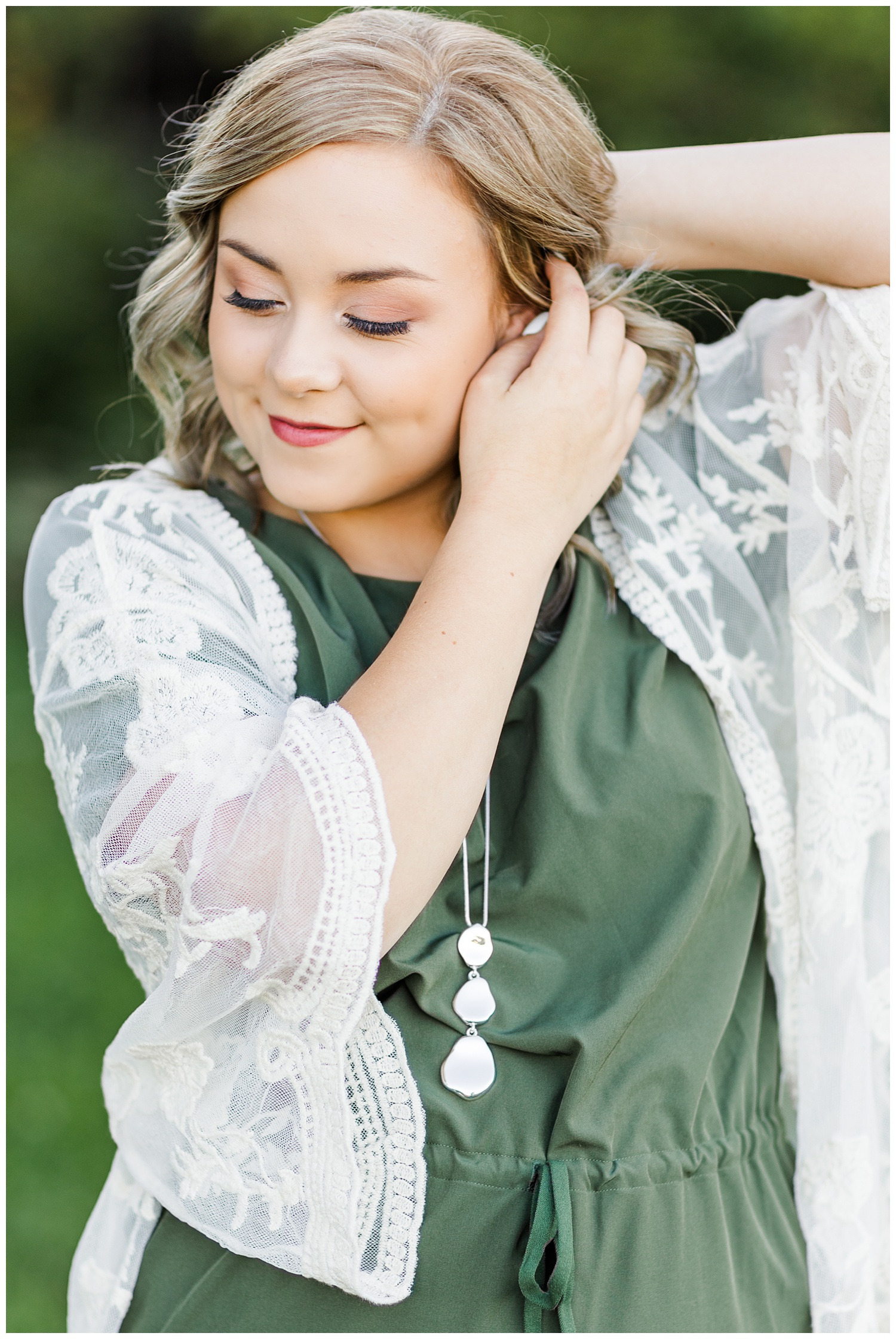 Cloey, wearing a green dress with a cream lace kimono, slowly tucks her hair behind her ear while looking down   CB Studio