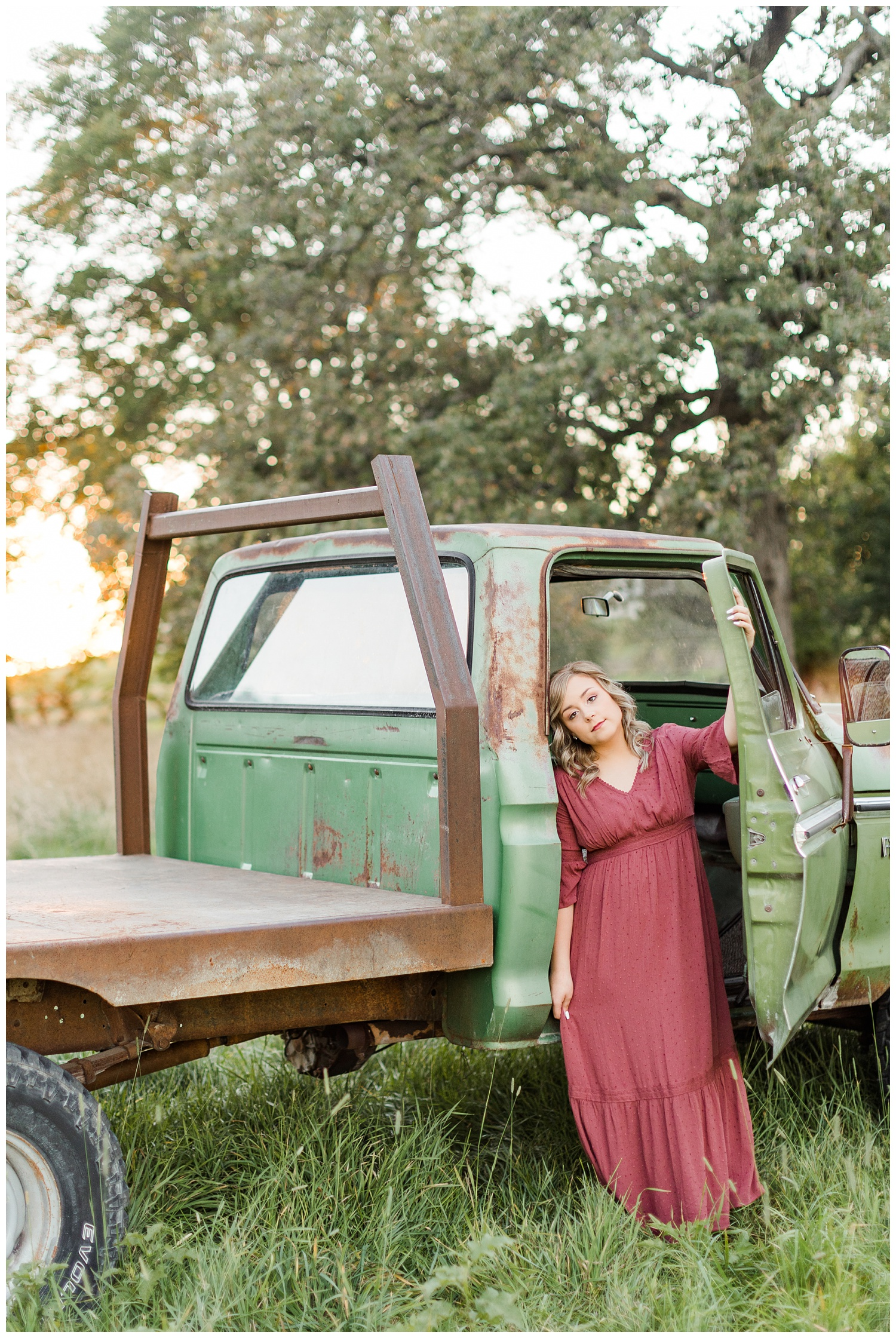 Cloey, wearing a vintage red dress, leans against the passenger doorway of an old rusty truck   CB Studio